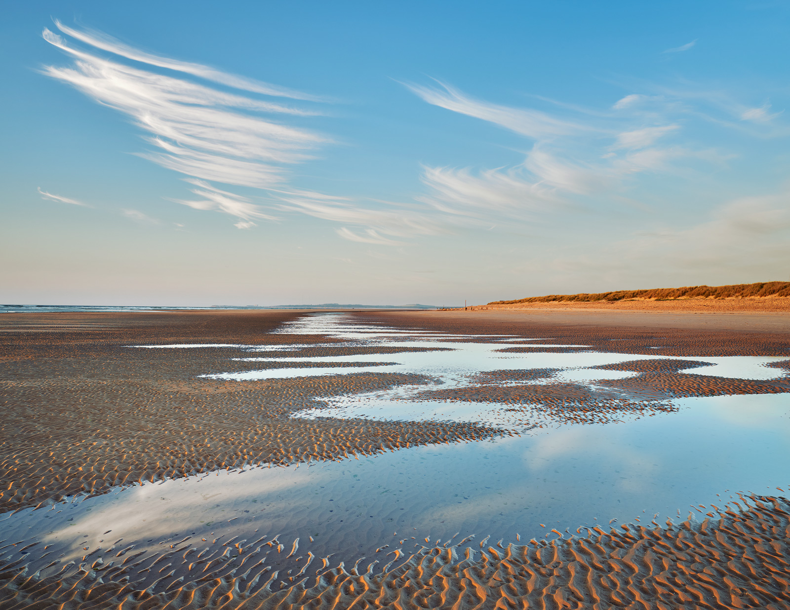 Cirrus clouds form above Findhorn's sandy beach before sunset on the Moray Coast.