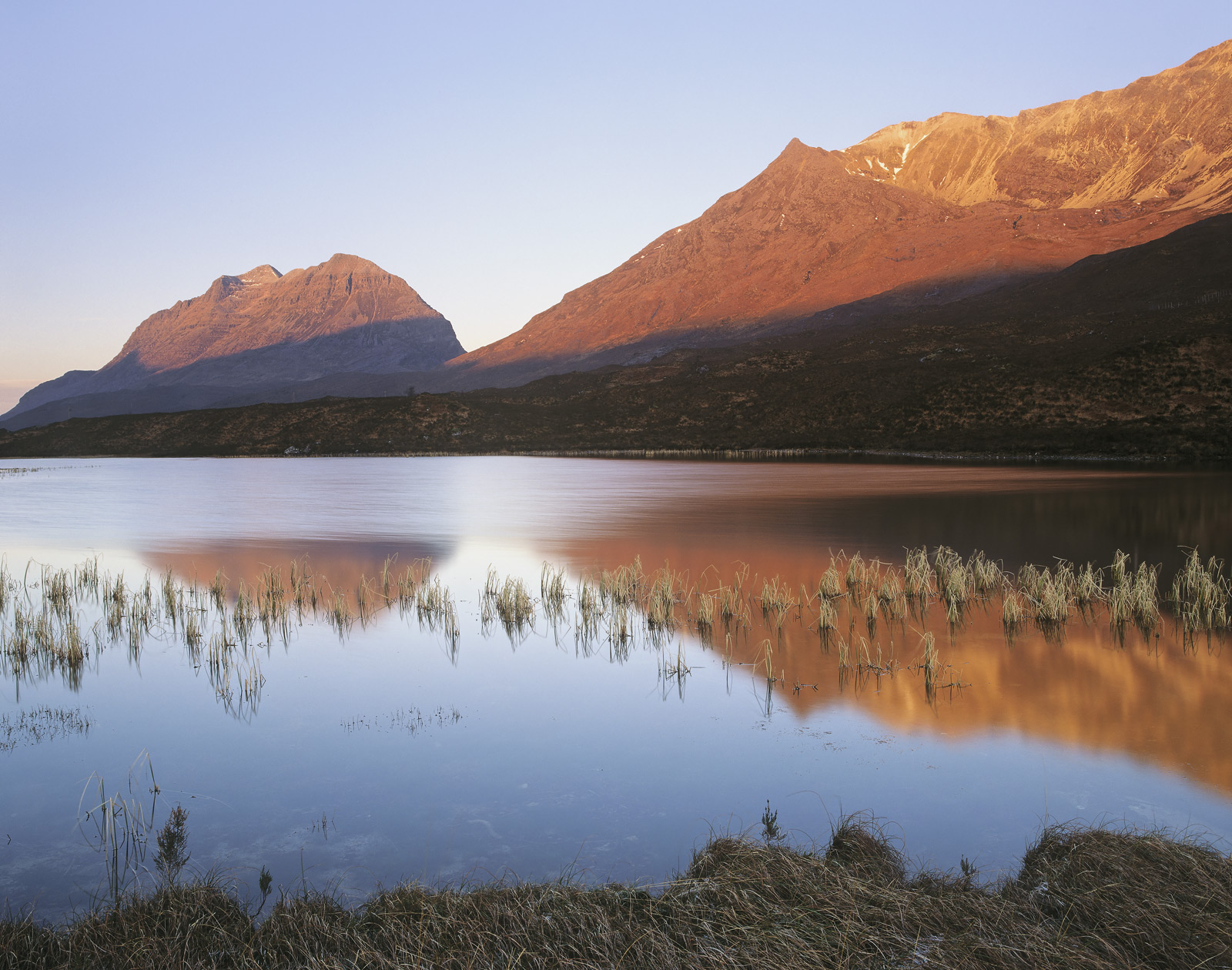 Carrot coloured early morning sunlight plays over Liathach and Beinn Eighe which in turn forms a lazy reflection in the surface...