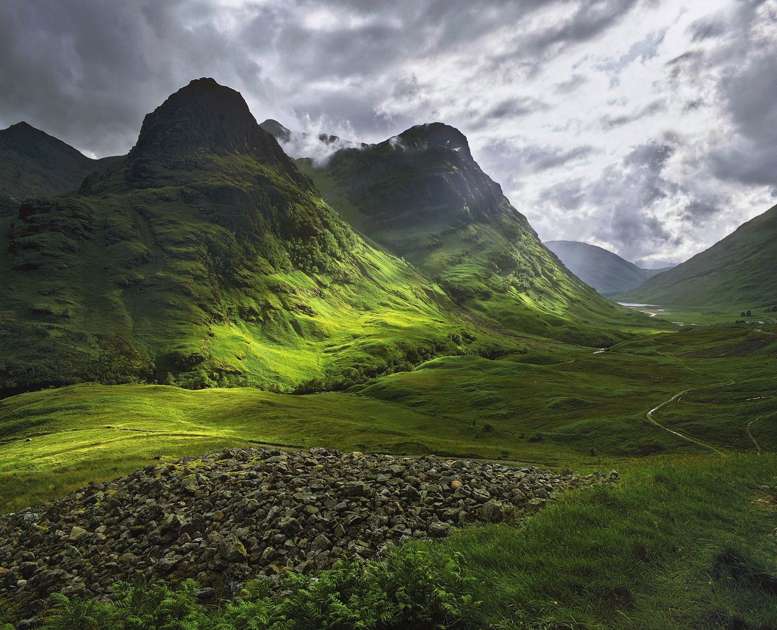 A shaft of sunlight breaks through low clouds around the Three Sisters on a spring afternoon and cuts a swathe of light across...