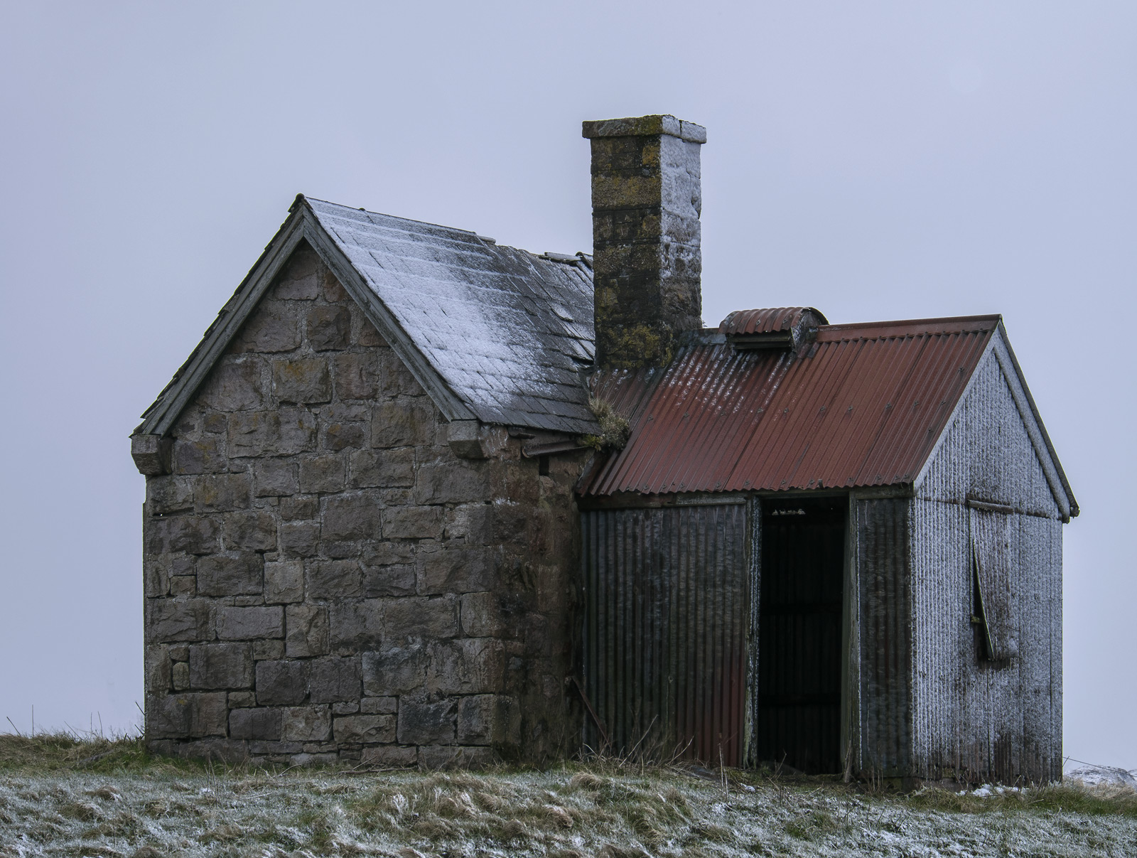 The cold twilight and winter grey sky make a compelling cold contrast to the warmth of that rusty red roof on that delightful...