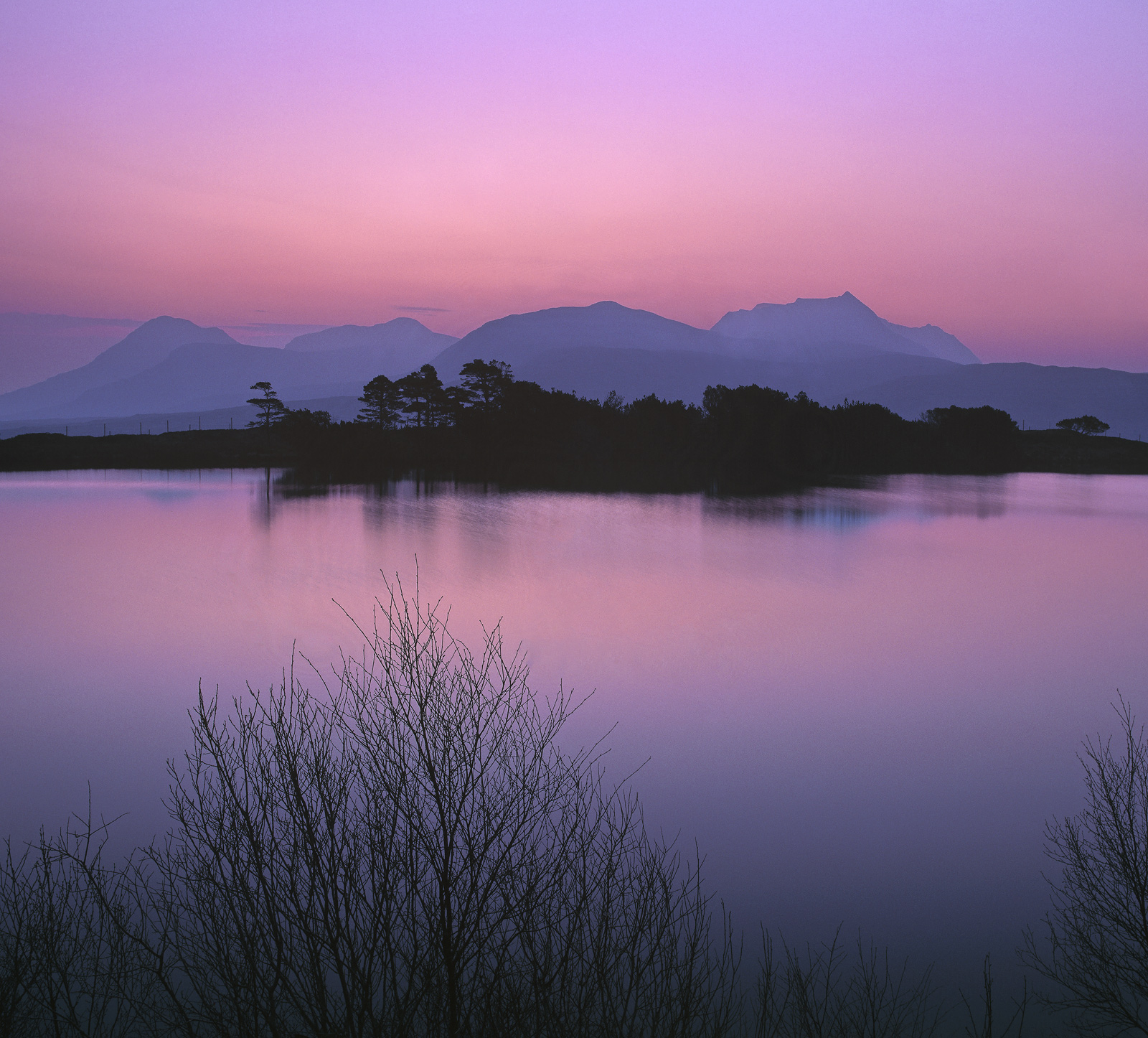 Glorious pink hues from a sumptuous plum coloured twilit sky bleed slowly into the midnight blues of dusk at Loch Culdromman...