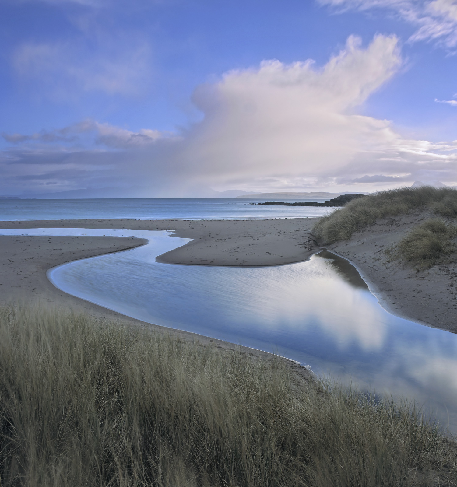 These gorgeous sinuous curves of water from a meandering peat stream carve their way through Mellon's red sand beach down to...