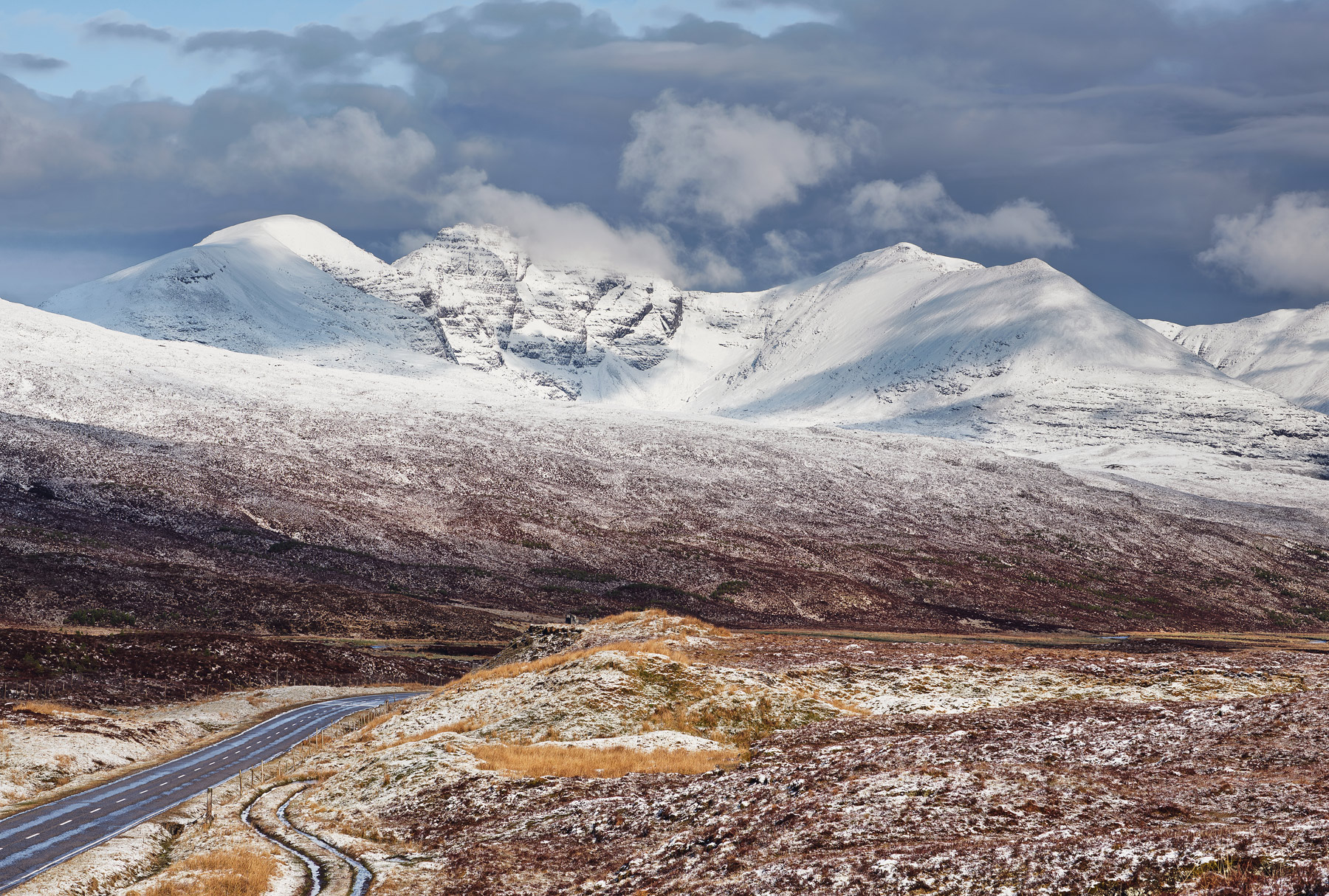 Snow clad mountains, dappled sunshine and dusted icing sugar on mighty An Teallach near the Braemore Junction, close to Dundonnell in late Spring