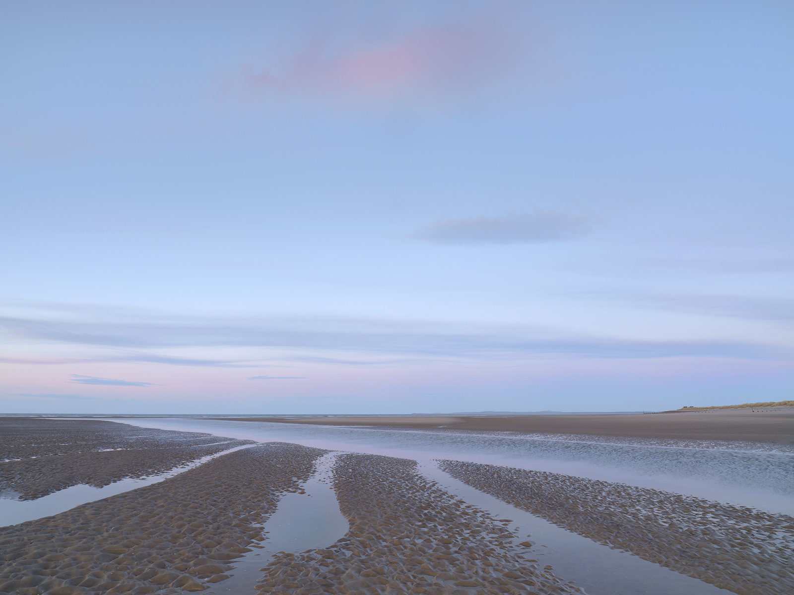 Twilight pastel pinks and blues displayed after sunset beside the outflow of the Findhorn river at Findhorn bay by the Moray Firth.