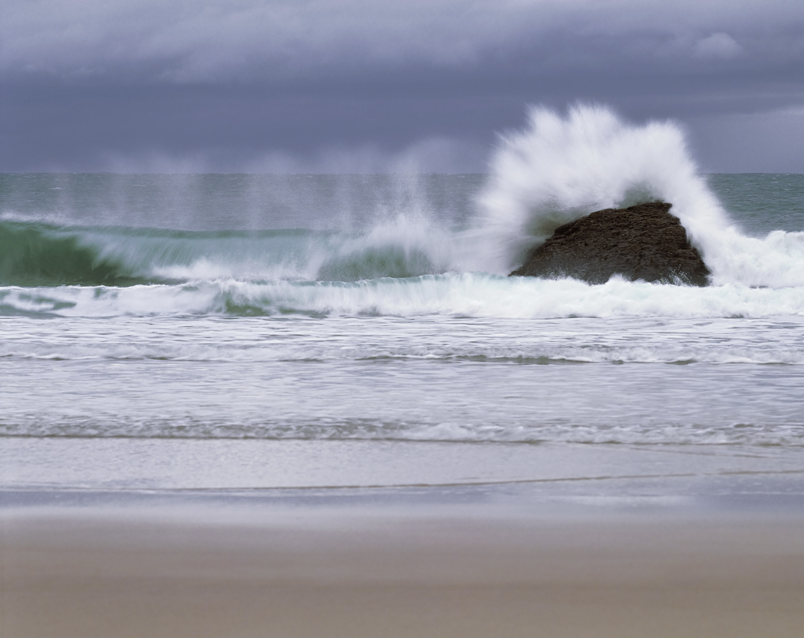 Huge rolling waves amidst a fierce offshore wind blew back plumes of spray from the cresting waves as they smashed against the...