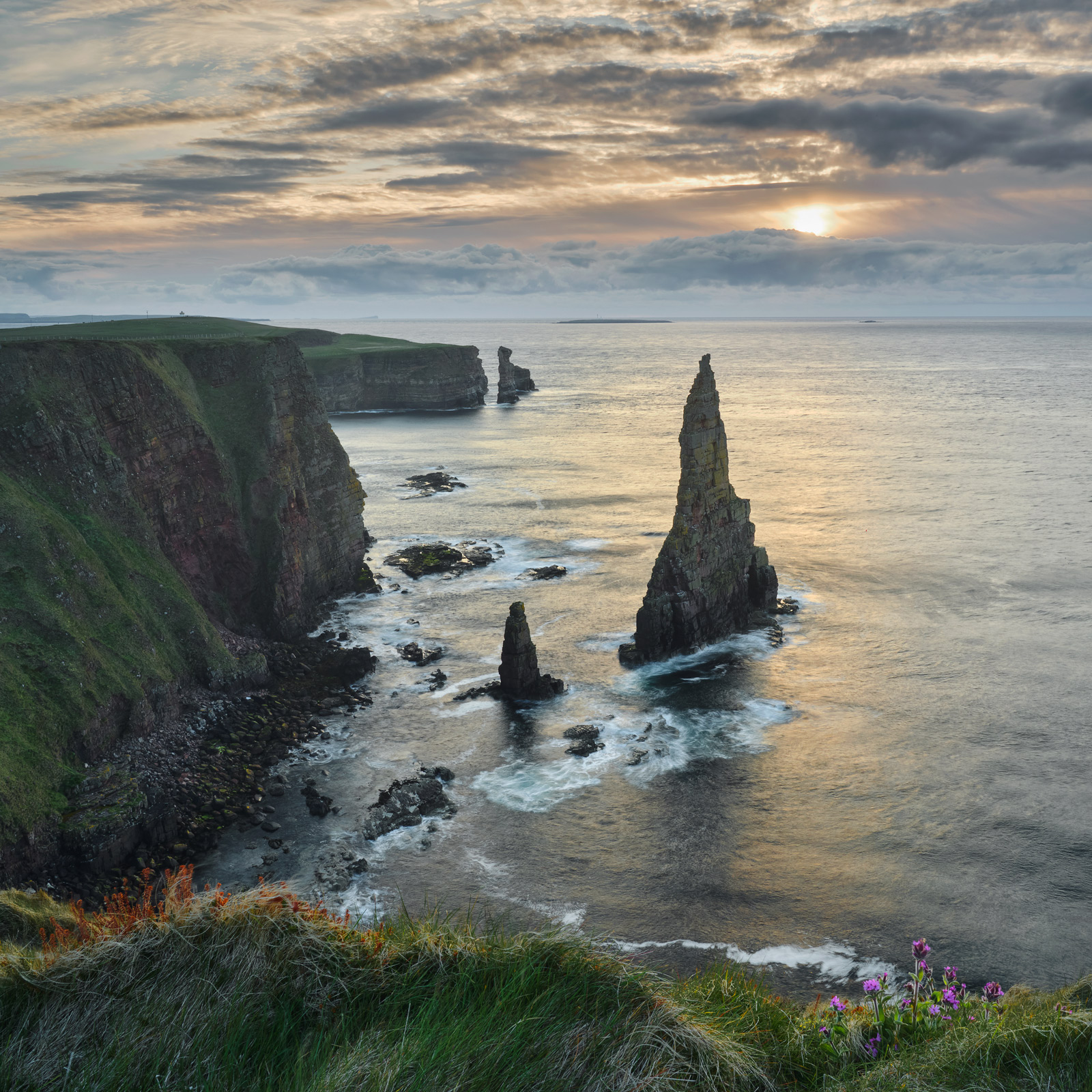 A watercolour sunrise following a long walk to a cliffside view over the dramatic Duncansby sea stacks at Caithness.