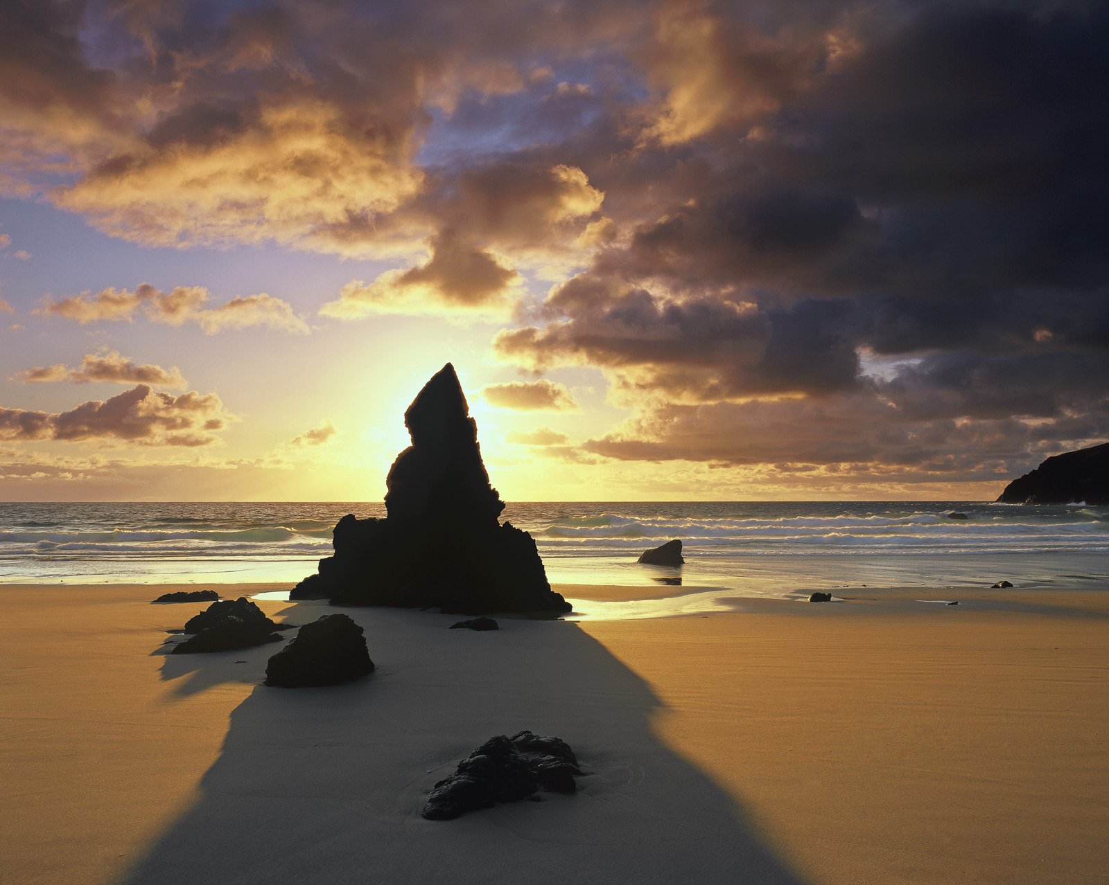 The shadow of a black tooth of rock blocking a spectacular sunrise over the golden sands of Durness beach on a glorious summer...