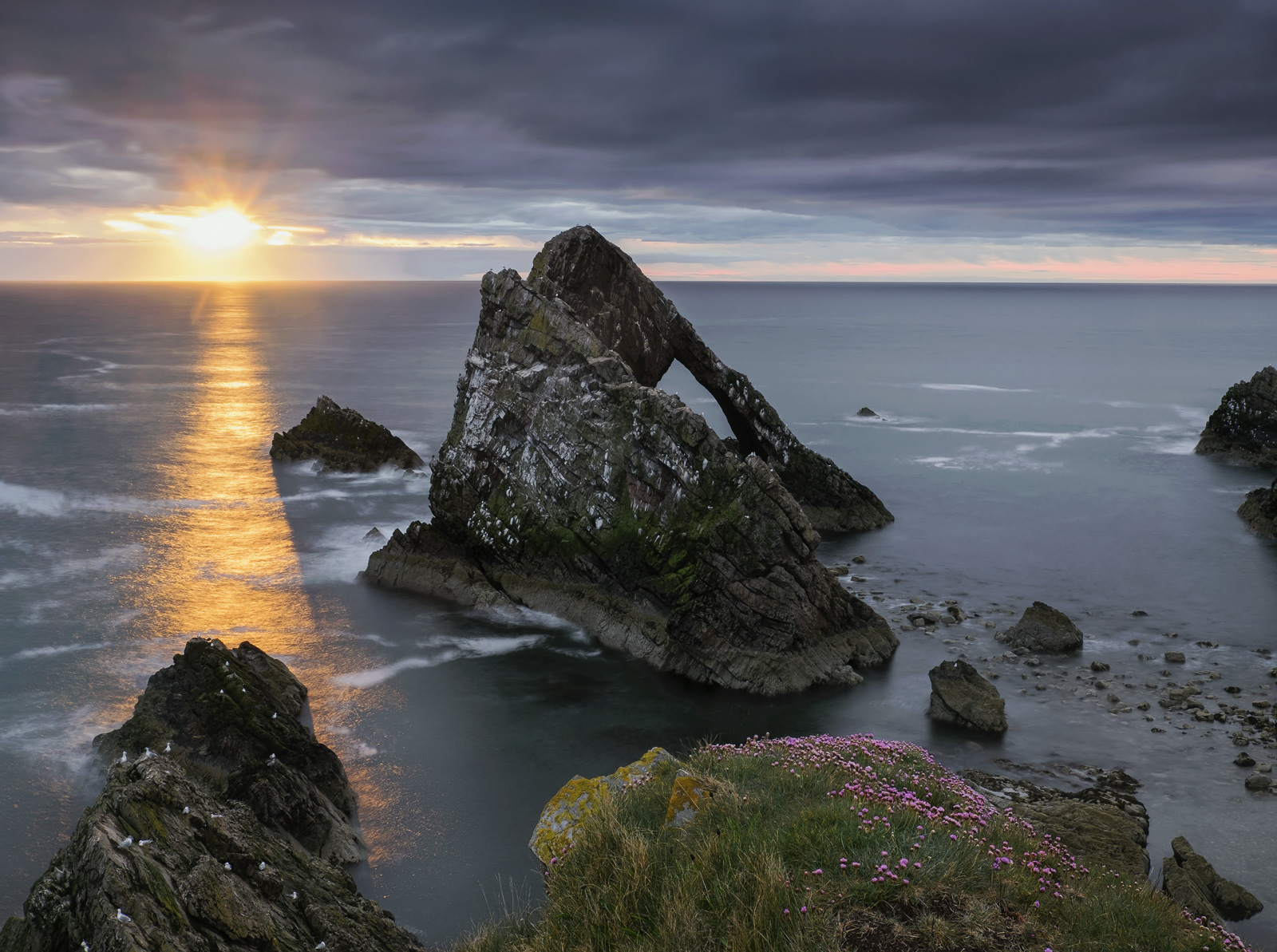 A reluctant summer sunrise over the Bowfiddle rock with pink nodding thrift adorning the top of the cliffs.  A beam of transient...