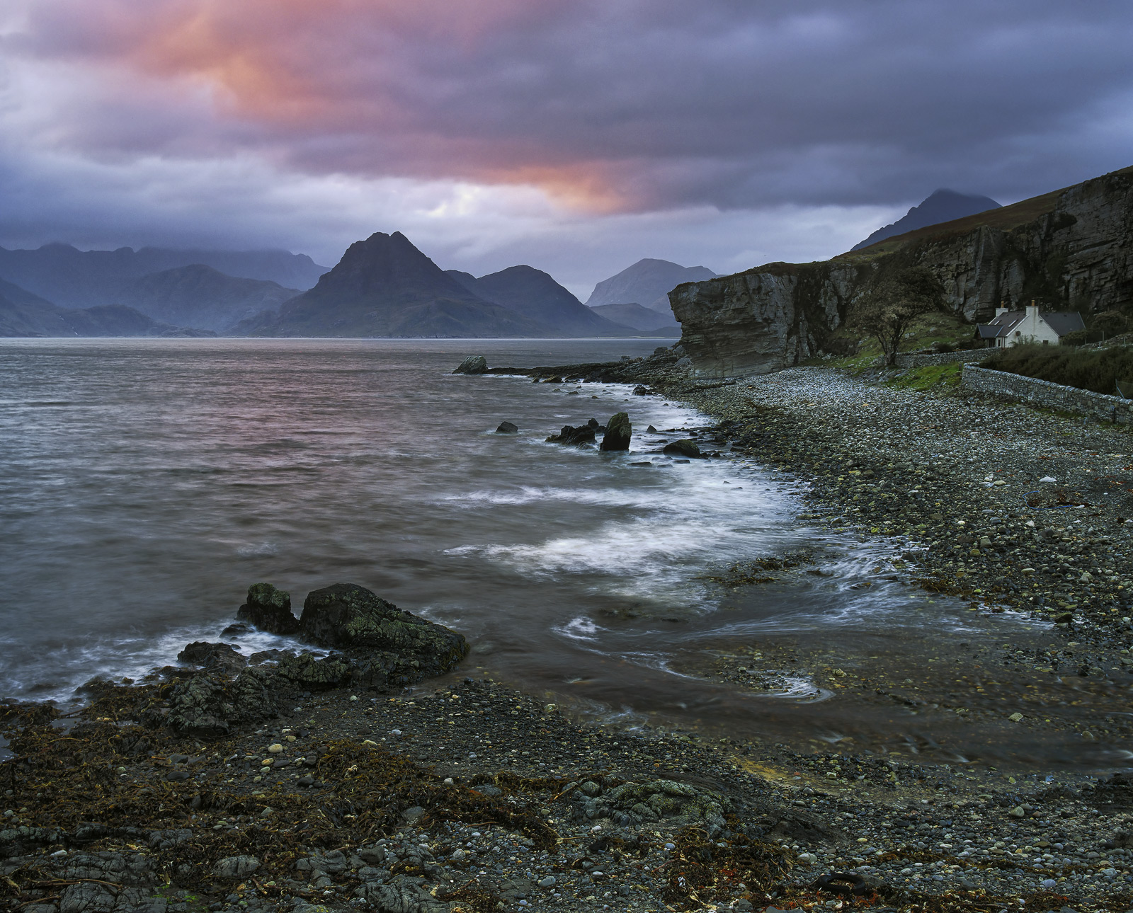 Twilight settles over Elgol and some of the higher clouds start to redden over the distant Cuillins.