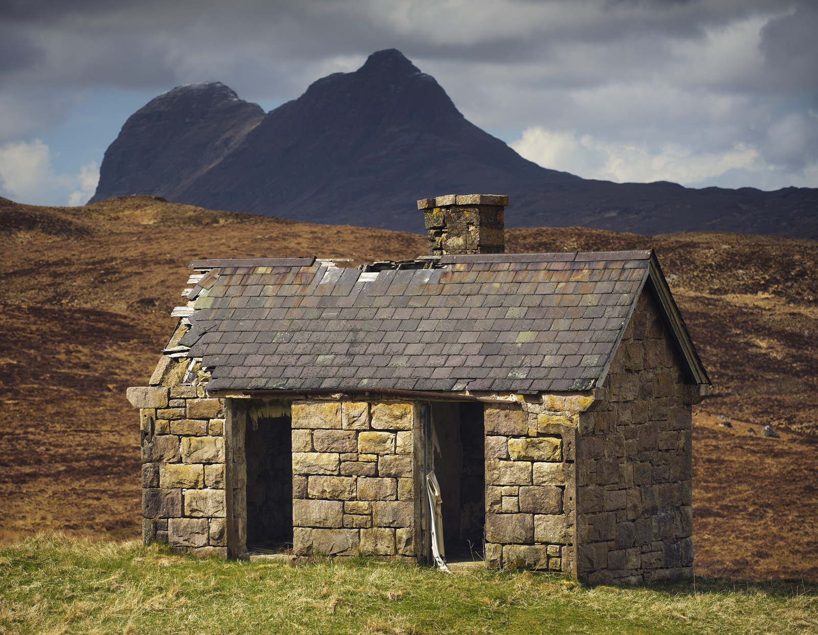 The sunlit weathered derelict stone hut at Elphin in the shadow of Suilven