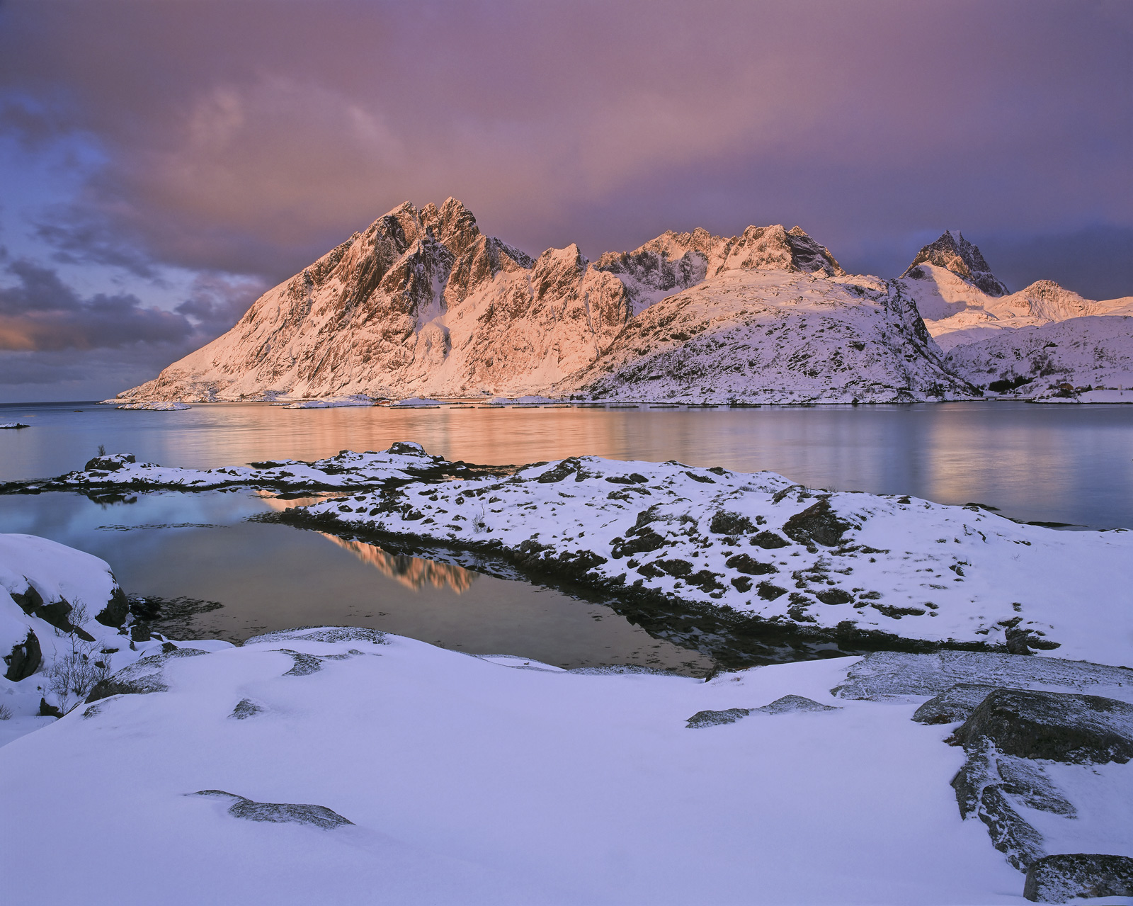 Strawberry coloured sunlight struck the snow laden summits around Reine across the fjord from Sund an old whaling station.&nbsp...