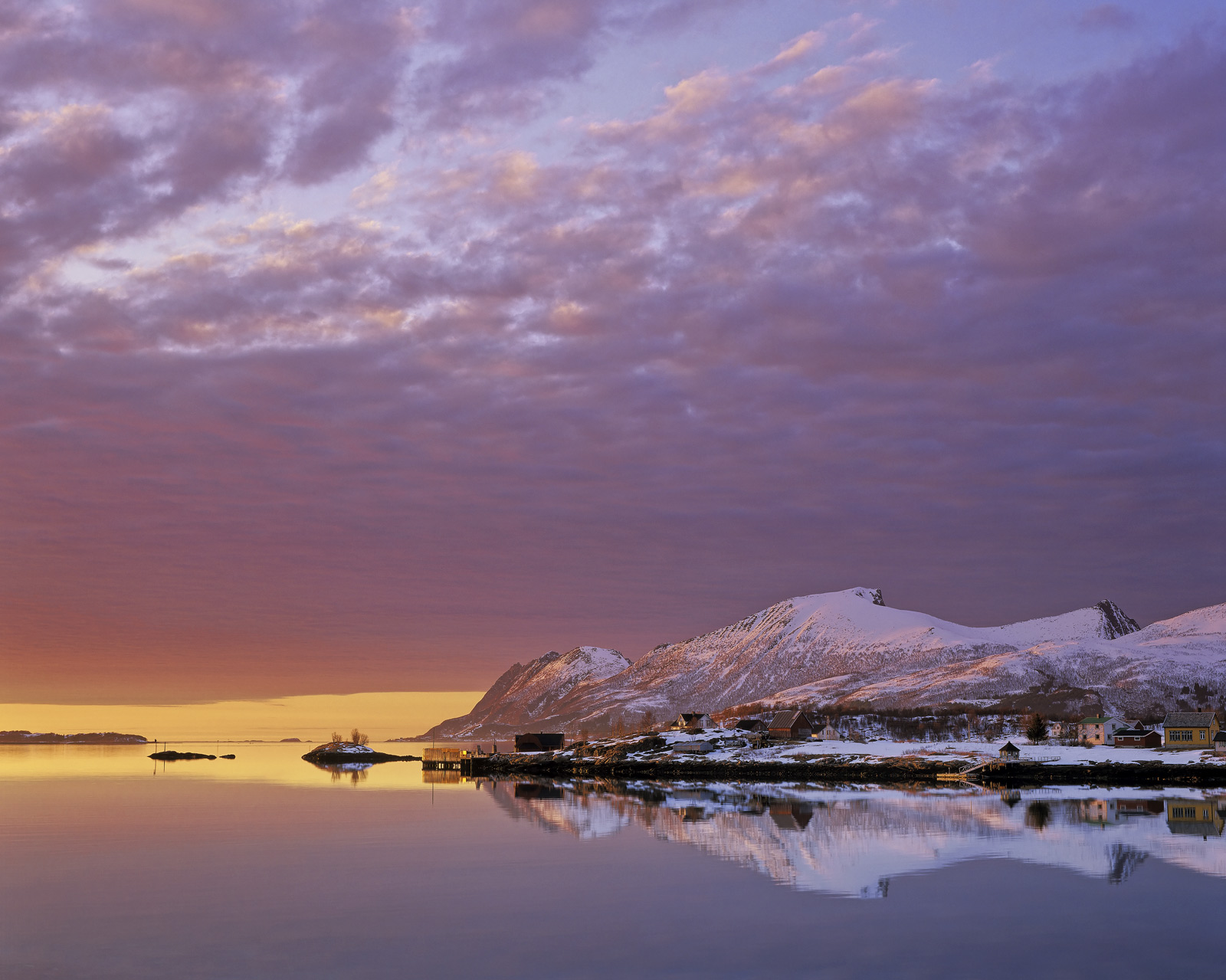 A glorious slice of mango separated lilac clouds during this exquisite sunset at Senja Island in Norway. The snow dusted...