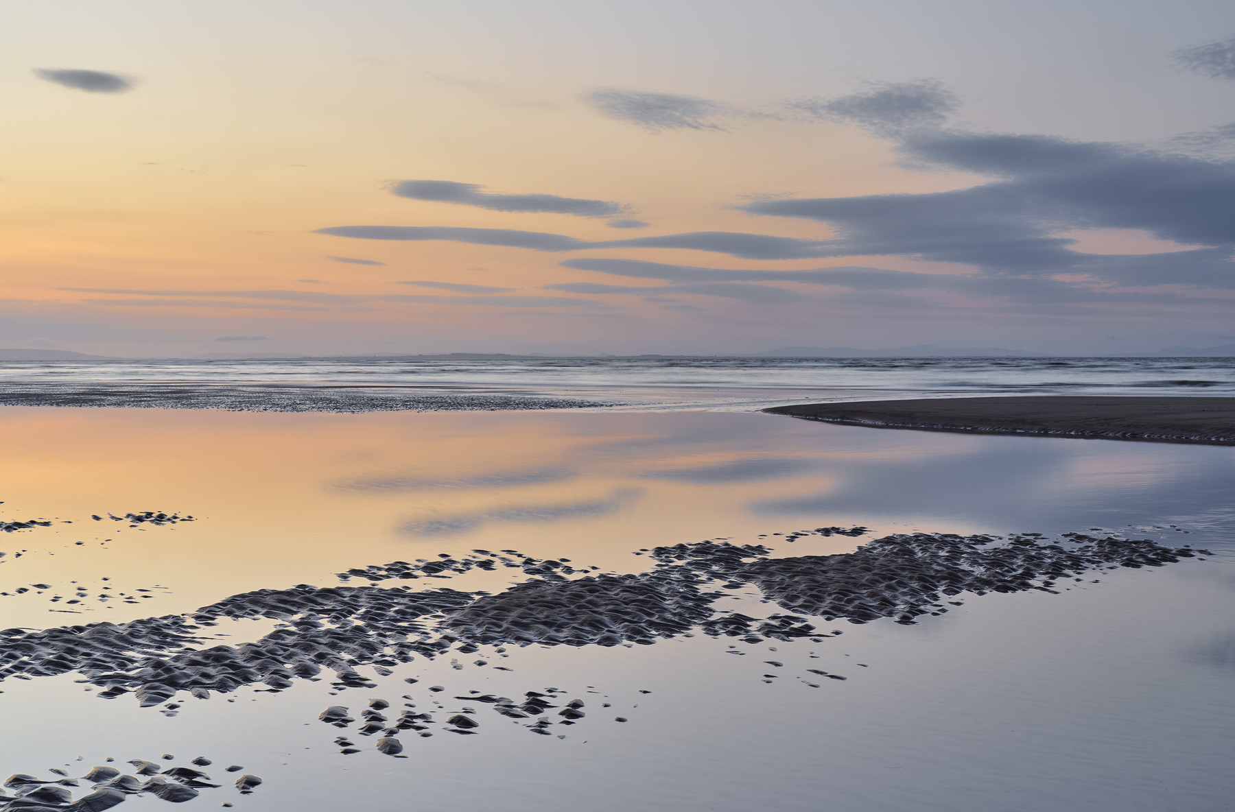 Soft glowing twilight colours of dusky orange and blue reflected with the clouds in a thin skin of smooth and unruffled water at the tide margin