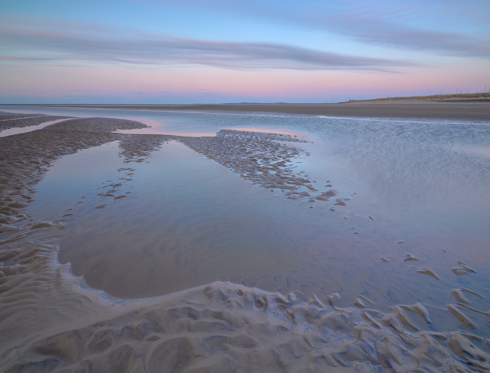 soft pastel colours of pink and blue at dusk on the beach at Findhorn in Moray, Scotland.