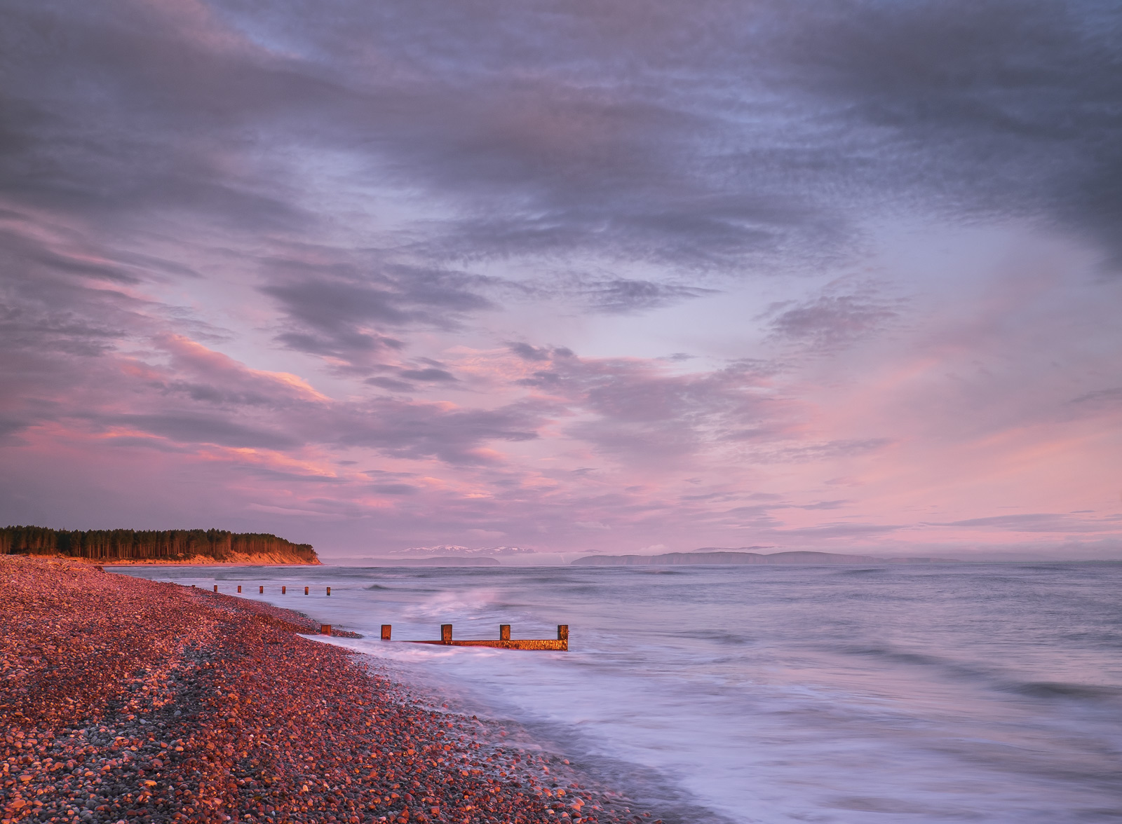 A high tide on a late Spring morning dawns with a sky so vibrantly red that even the beach opposite the rising sun is stained...