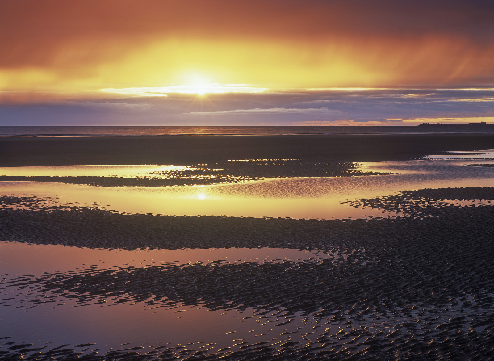 A glorious sunrise over Burghead as viewed from Findhorn beach across shallow depressions and rivulets in the soft sand of the...
