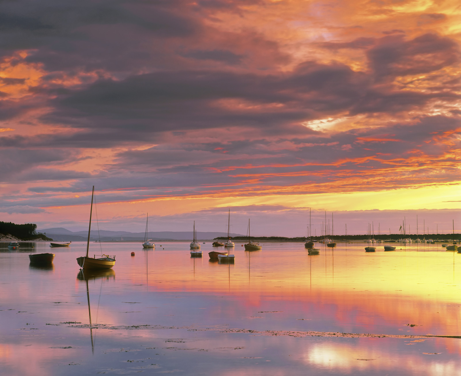 A fiery red sunset at Findhorn bay near the mouth of the river Findhorn. Sunset coincided with the turn of the tide and...