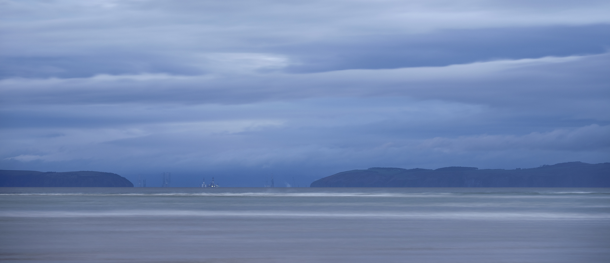 Twilight over the oil rig nursery at the Inverness end of the Moray Firth as viewed from Findhorn Bay in Moray at dusk.
