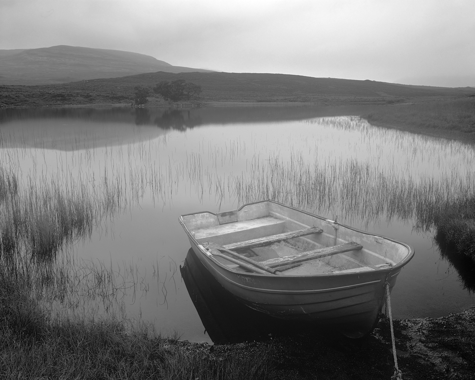 This little loch probably seems a tiny bit sad and dreary and the wee blue row boat with its peeling paint adds to the sense...