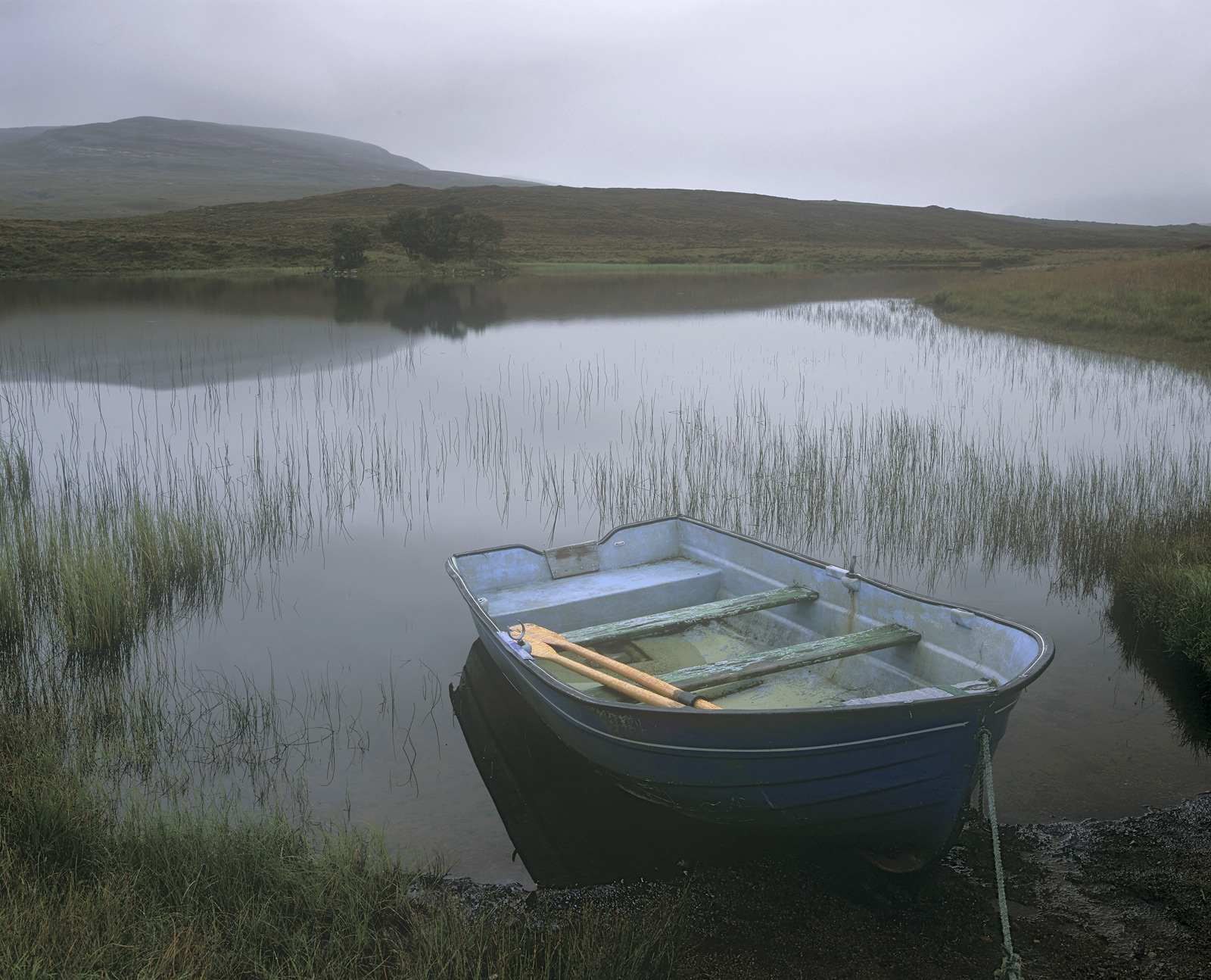 This little loch probablyseems a tiny bit sad and dreary and the wee blue row boat with its peeling paint adds to the sense...