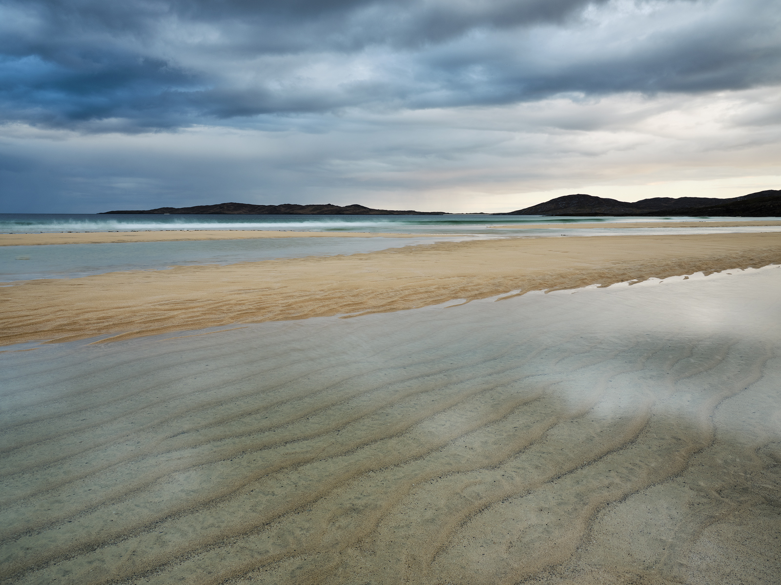 The deeply furrowed beach at Traigh Lar slowly fills with water at the return of the tide creating a beguiling mix of pale yellow sand and steely grey skies.