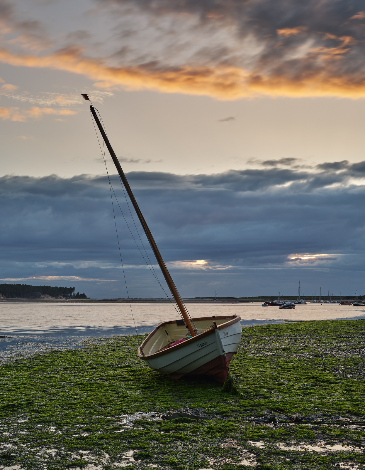 Vaarie an interesting wee wooden dinghy beached on the estuary at Findhorn on the Moray coast at sunset.
