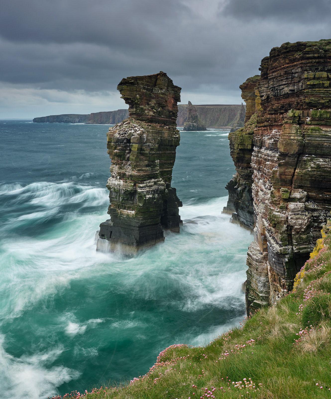 A huge turquoise sea roared around the isolated sea stacks and cliffs of the Caithness coastline creating plumes of spray beneath a heavy sky.