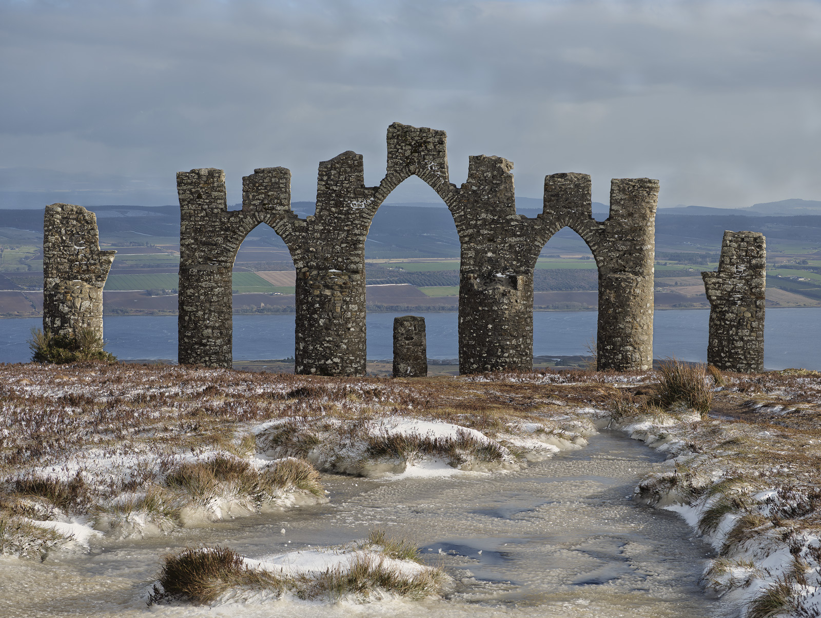 The unusual stone monument set upon a hill top at Fyrish above the Cromarty Firth and its resident oil rigs with ice and fresh snow dusting the ground.