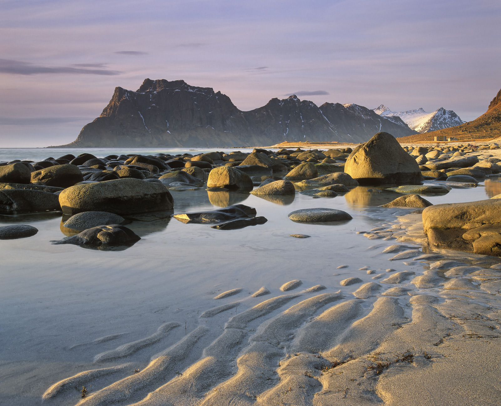 Rippled sand on the beach at Uttakliev in the Lofoten islands leads past rimlit smooth boulders burnished gold by the late afternoon...