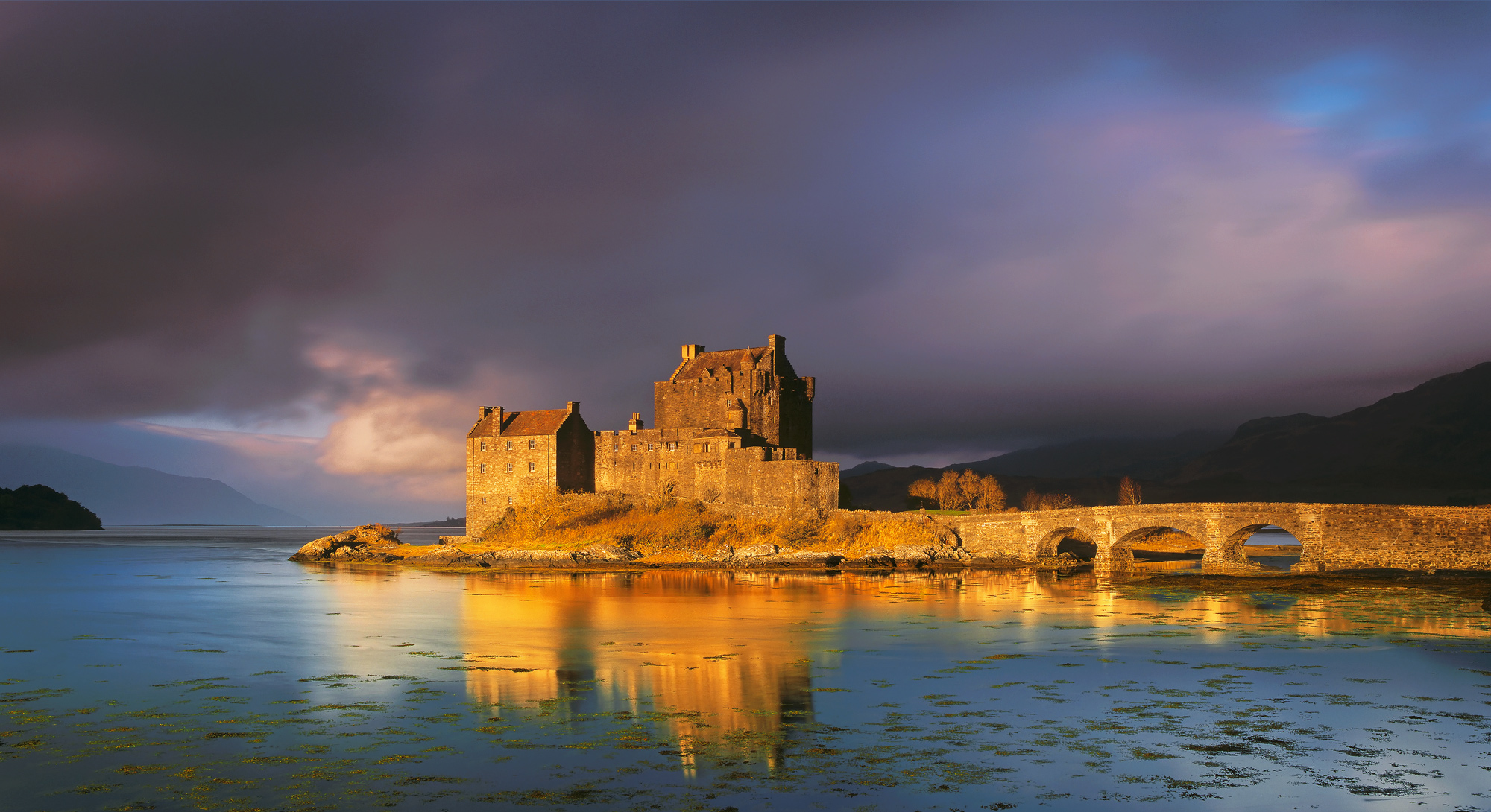 Golden light at sunrise struck the flanks of Eiean Donan Castle just seconds after a biblical deluge all but concealed the castle and the view beyond.