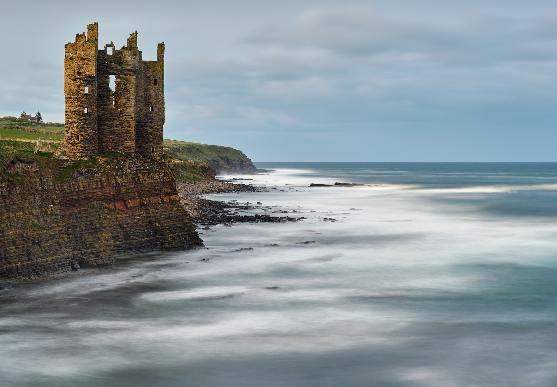 Sunlit Keiss castle flickers gold in the end of day light perched high on a cliff directly overlooking a boisterous sea at high tide.
