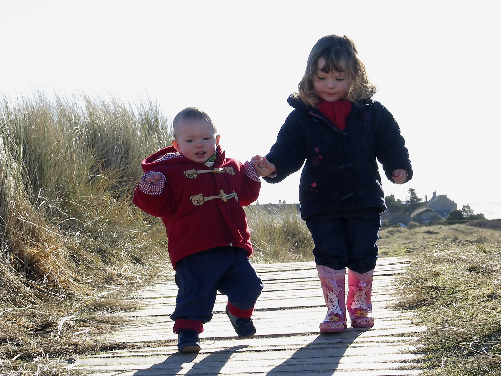 Lauren aged four and Ben aged two toddling down to their favourite beach backlit against the sun as usual the bright sunshine...