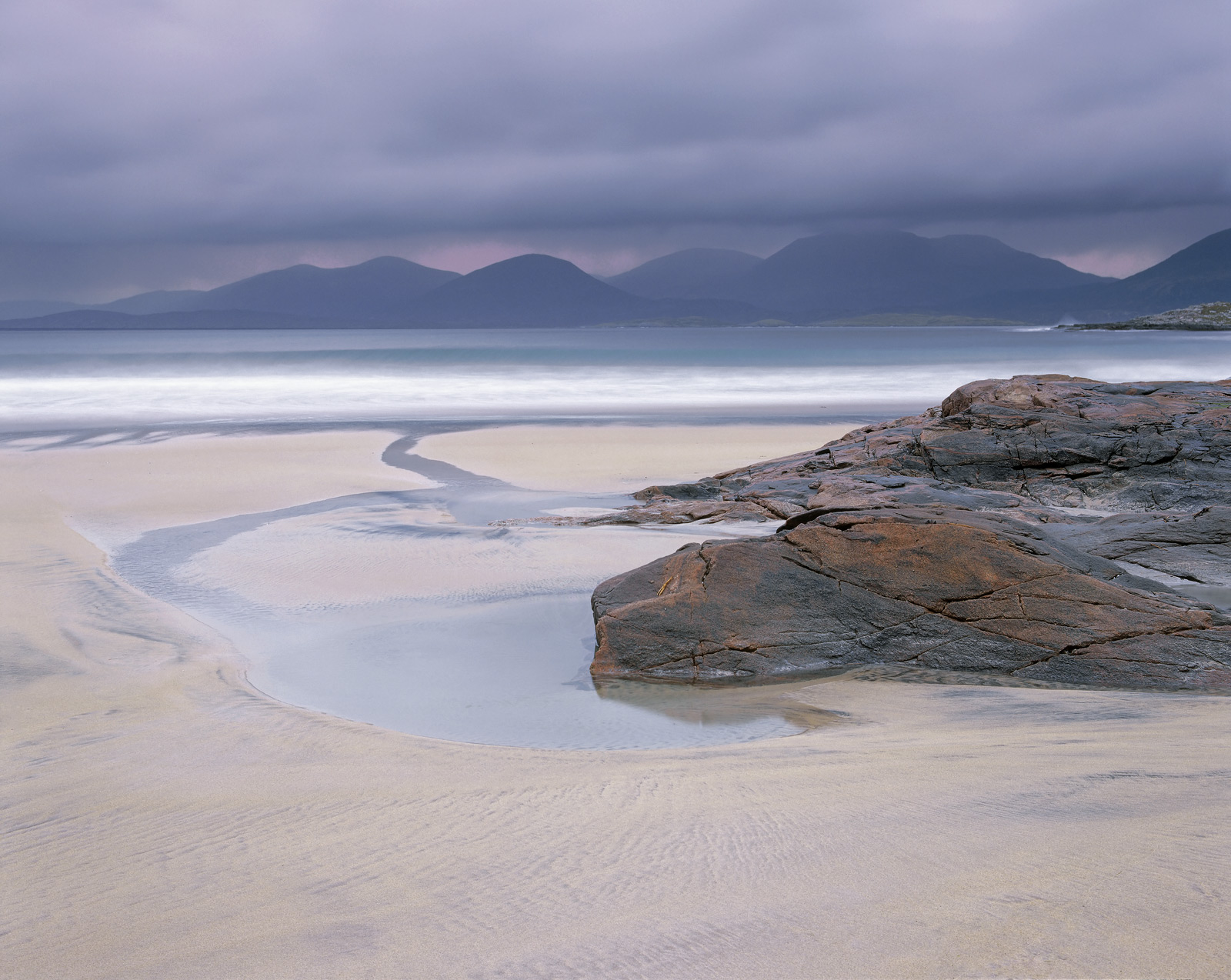 A heavy sky settled over the serrated teeth of Harris's distant peaks turning them a rich purple hue. The soft light at...