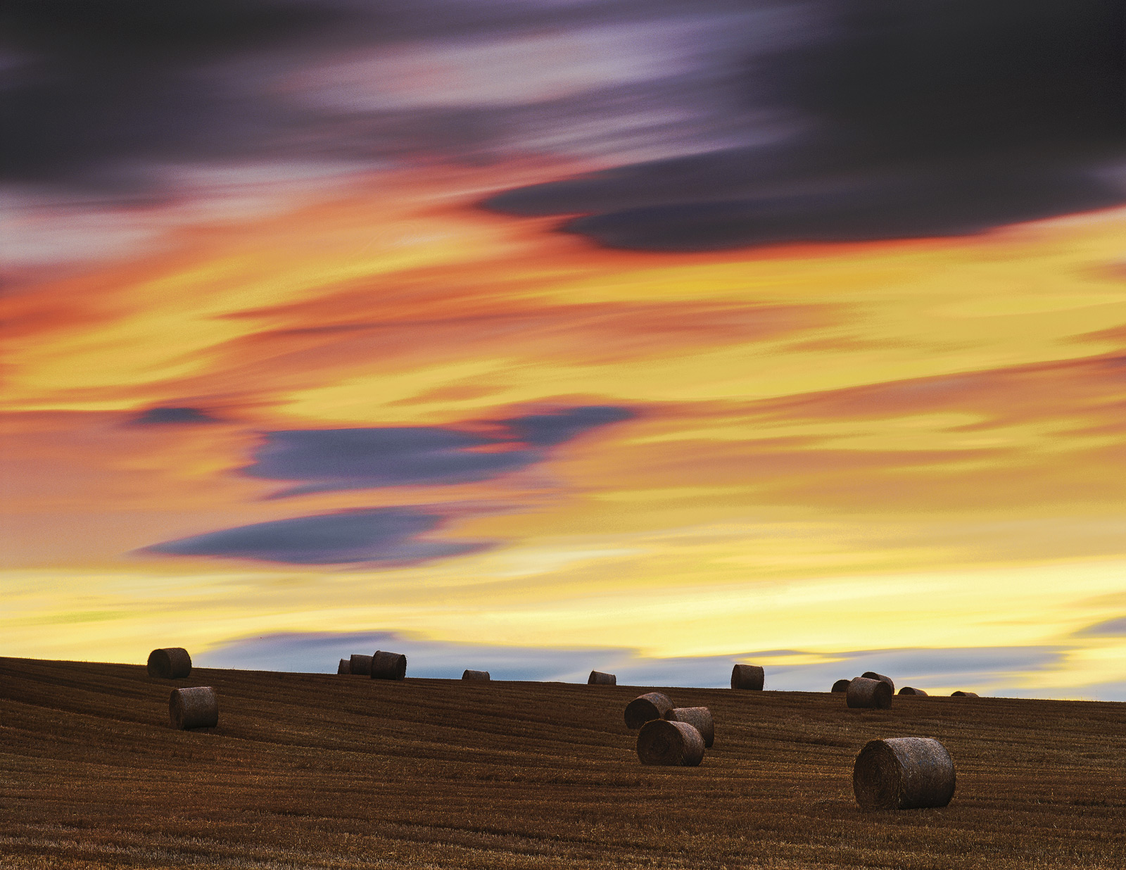 I found myself at the foot of a sloping field of straw bales which backed on to a glorious sunset sky. The simplistic composition...