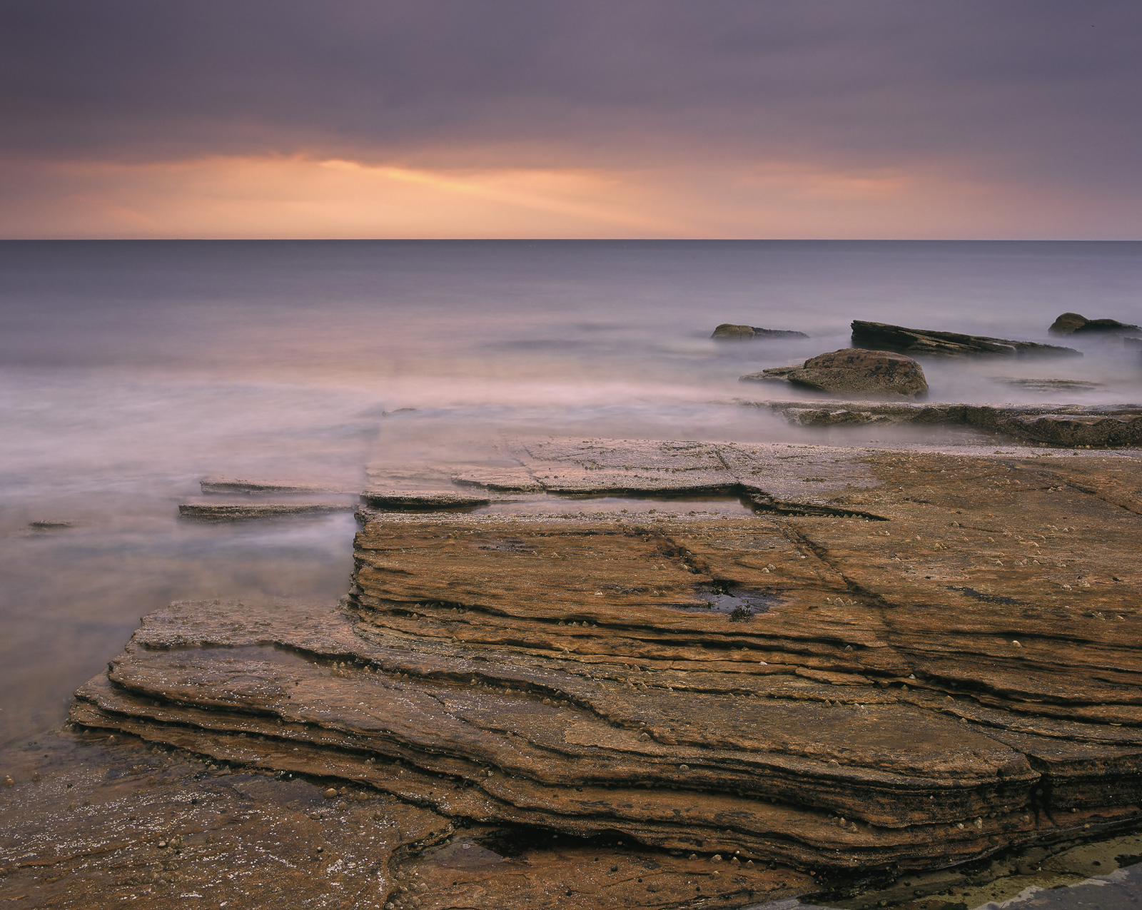 Pancake layered sandstone rocks at Hopeman bay on the Moray coast break off and peel away like ginger snaps while the setting...