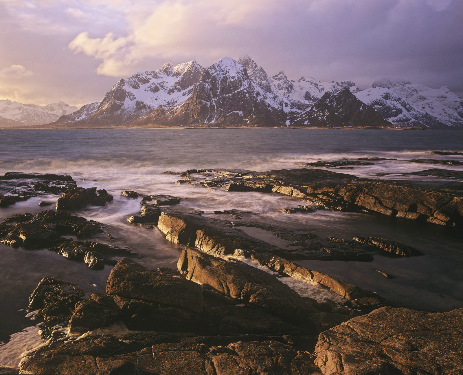 Warm evening sunlight belies the chilly conditions beside the foreshore that gazes out towards the stunning serrated peaks of...