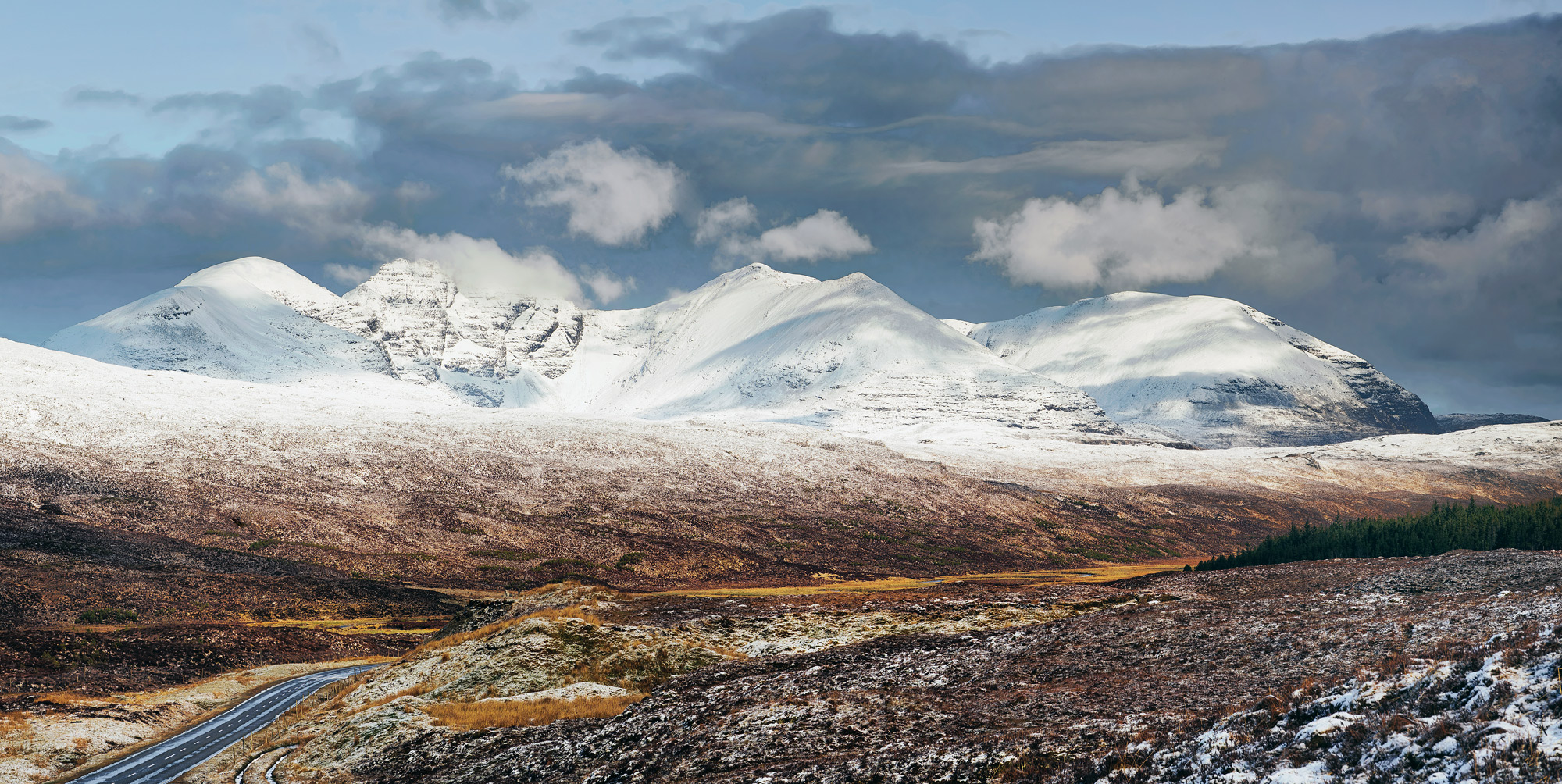 Snow clad An Teallach dappled with light and shade on the high road connecting Braemore Junction with Dundonnell