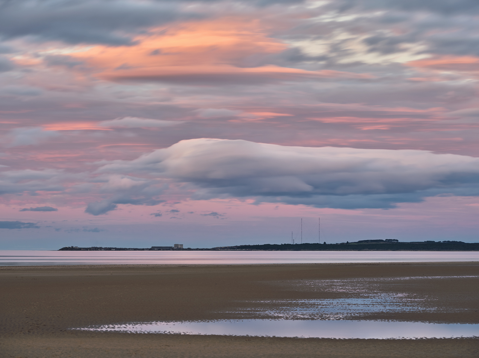 Salmon pink skies from a twilight wedge reinforce the delicate rainbow pastel shades of a stunning autumnal sunset above distant Burghead.
