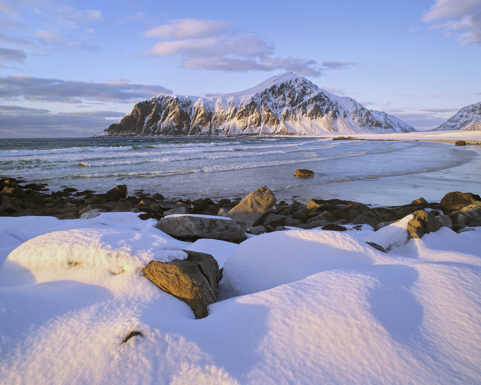 A low winter sun rakes it's way across Skagsand beach at Flakstad revealing every blue furrow and golden dimple in the fresh...