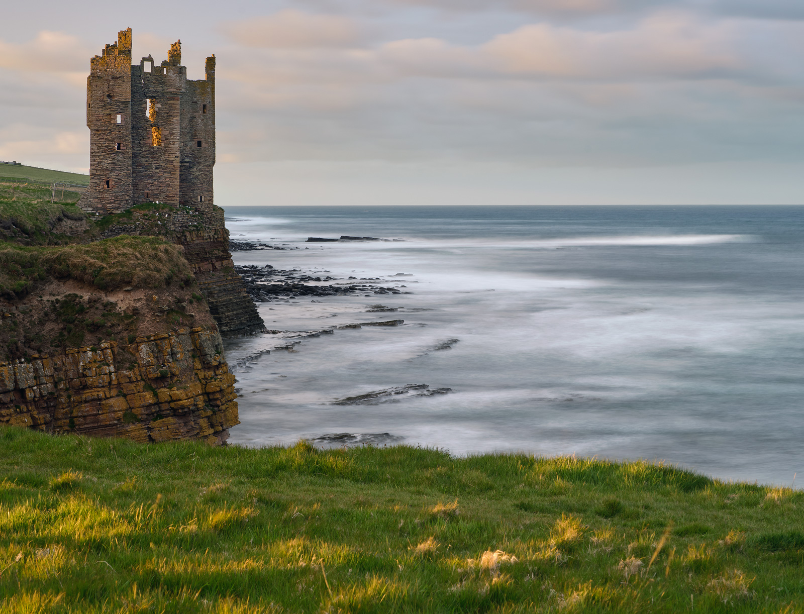 Sunset light flickers over Keiss Castle at high tide on the Caithness coast.