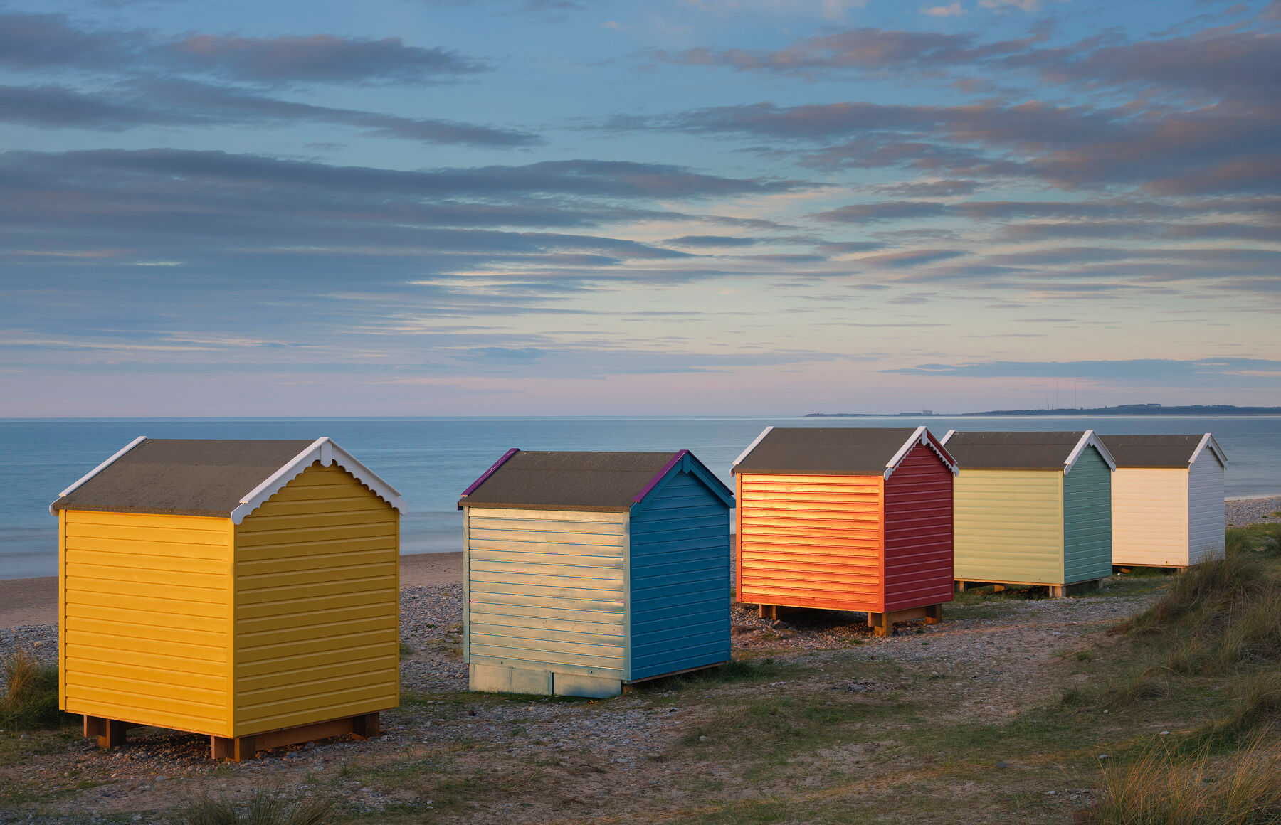 Rainbow coloured beach huts lit by the last rays of light from the setting sun at Findhorn bay on the Moray coast.