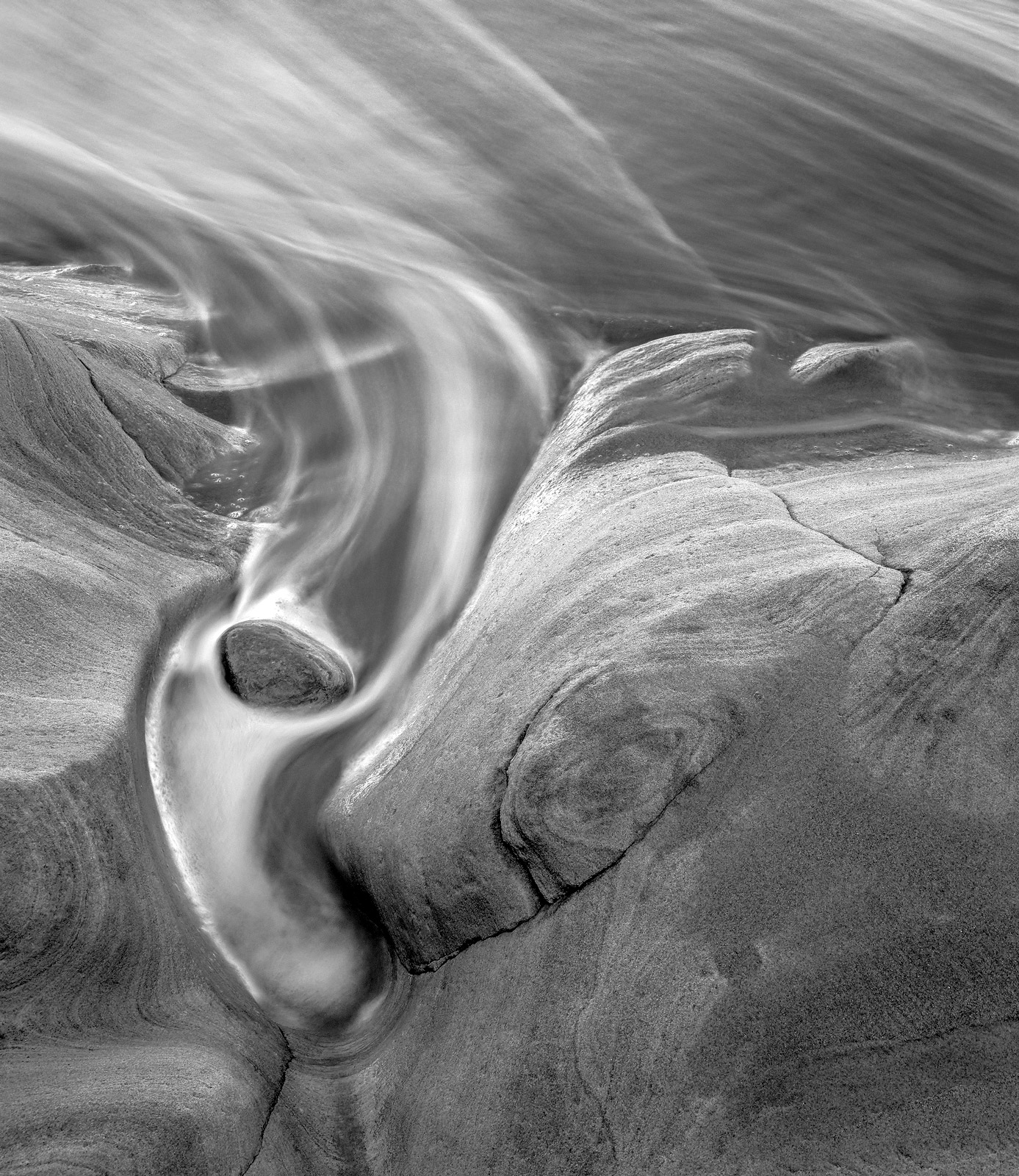Swirls of water receding from indentations in tide sculpted sandstones create fascinating patterns this monochrome version concentrates...