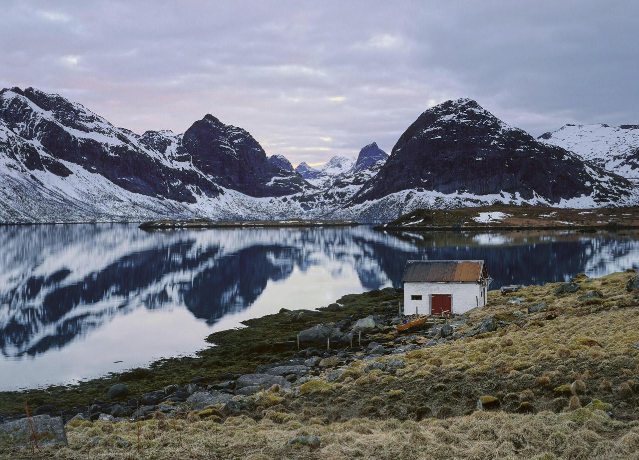 This little white fishing hut with rusty roof and drying cod hanging on the end walls was idyllically situated at the end of...