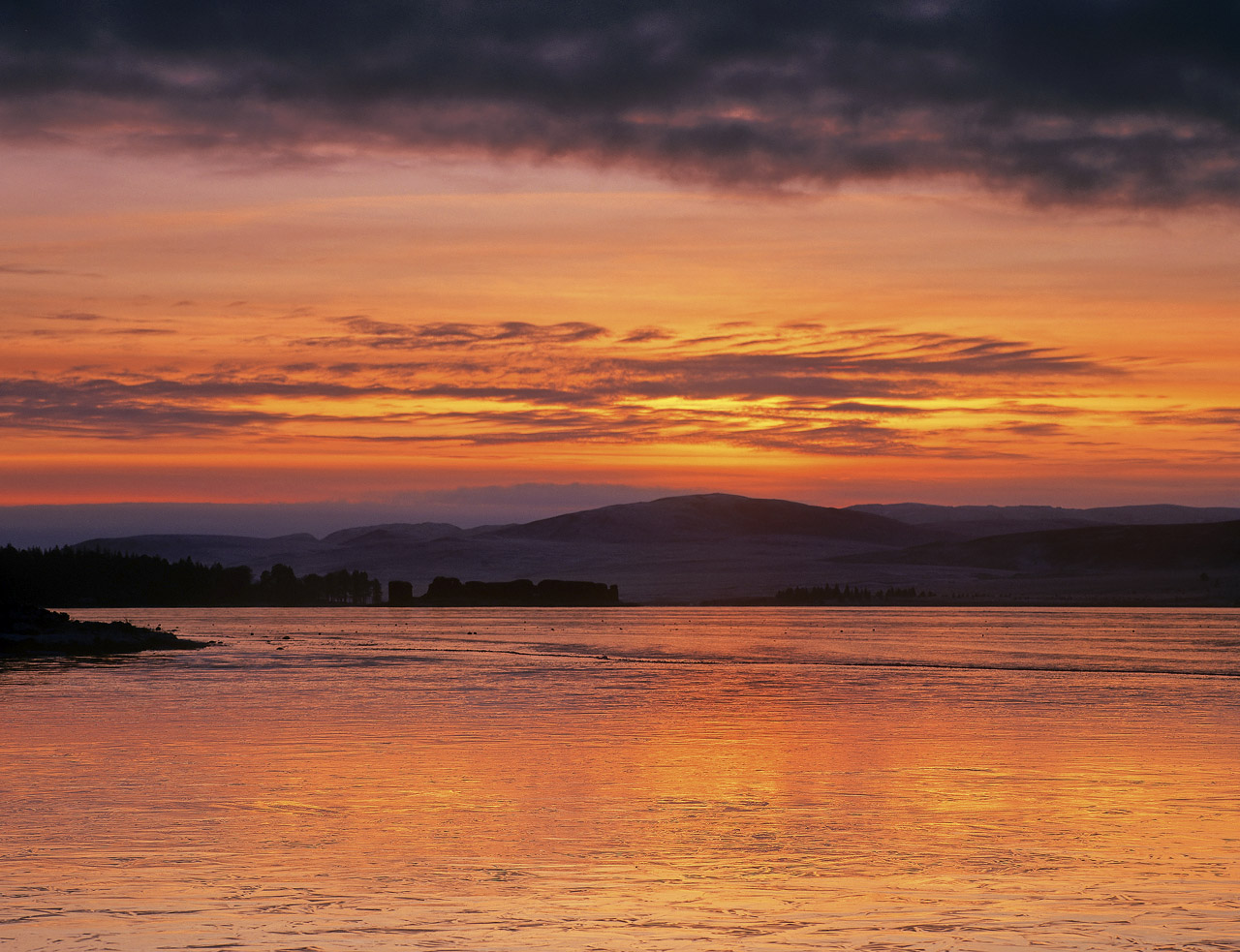 a glorious winter sunset over desolate and frozenLochindorb the colours reflecting spectacularly in the ice. careful...