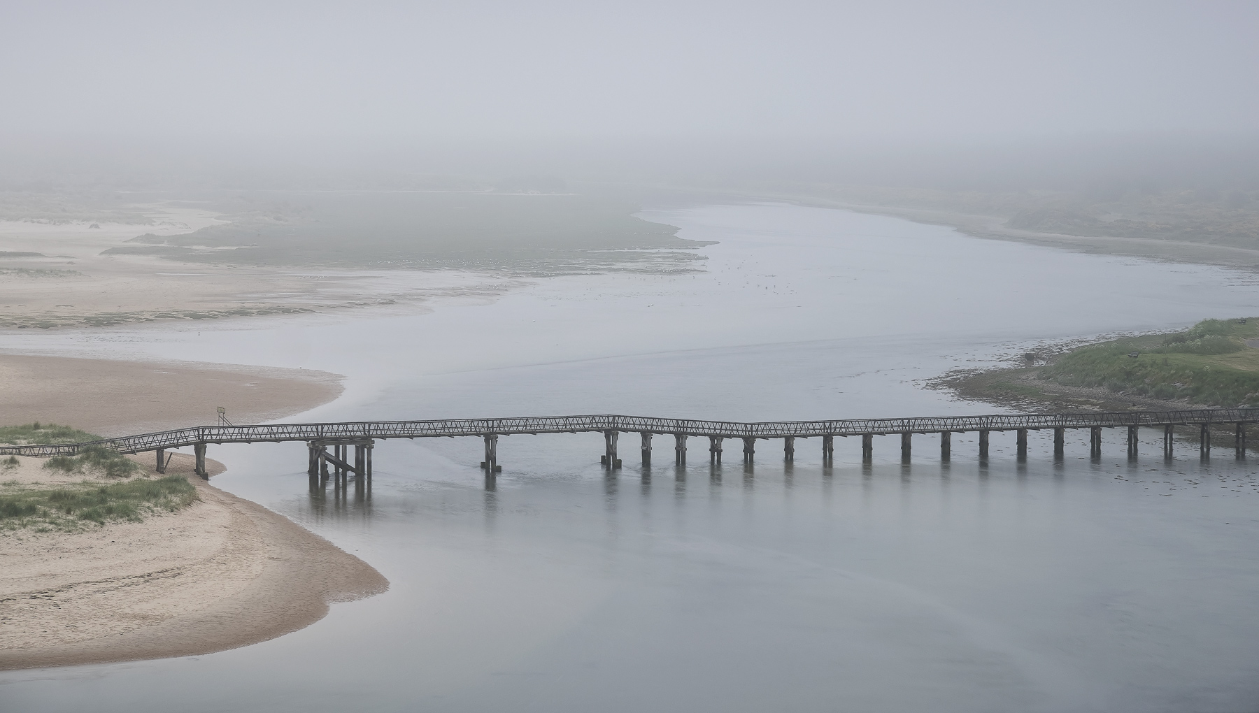 A thick grey carpet of fog and mist carpet the river mouth at Lossiemouth's east beach lending it an eerie atmosphere compounded...