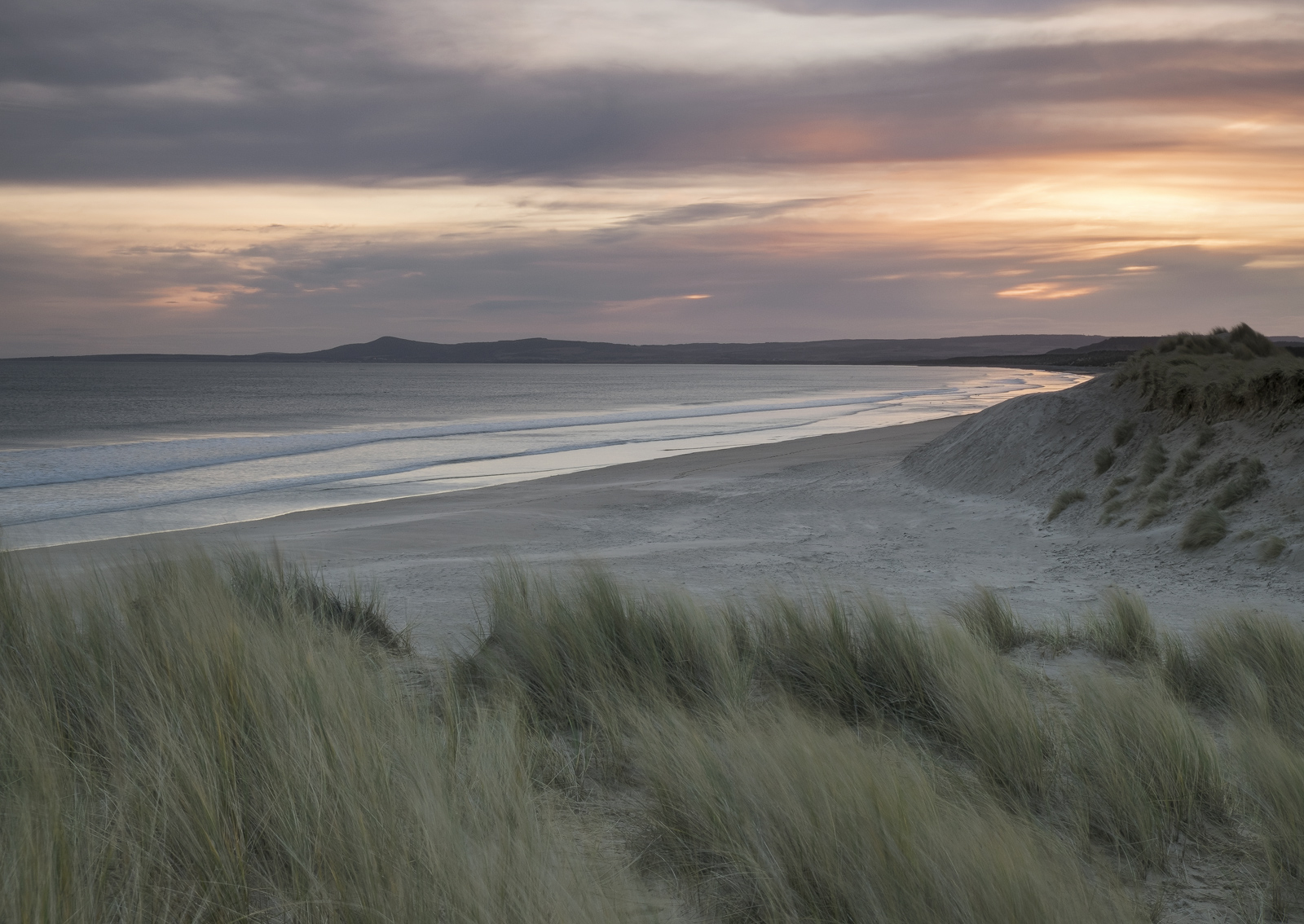 Soft winter light breaks over Lossiemouth's East beach at sunrise on a cold and chilly winter morning. I nestled atop one...