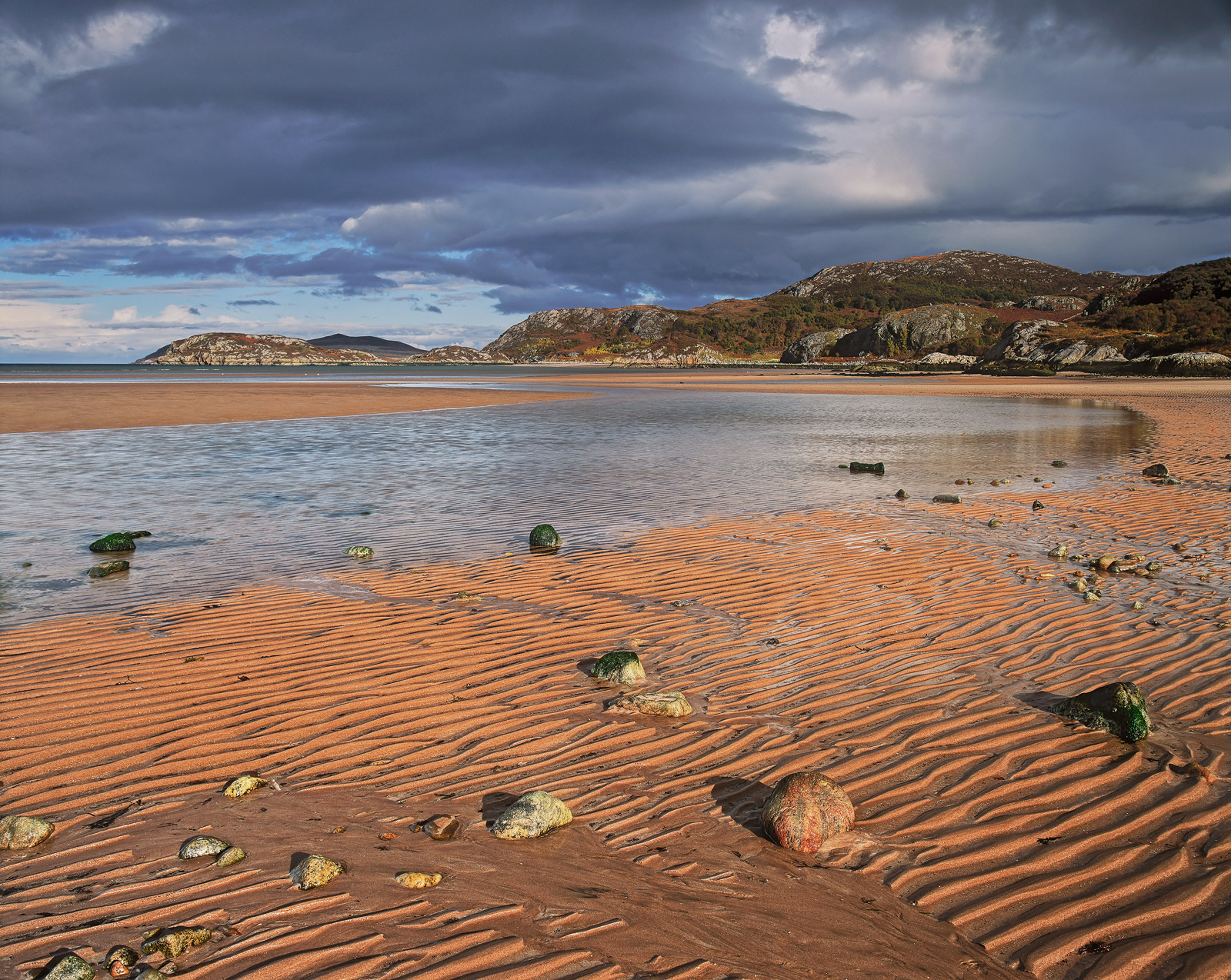 One of the most beautiful stretches of the west coast of Scotland.  Gruinard Bay at low tide shows a red sand beach often furrowed...