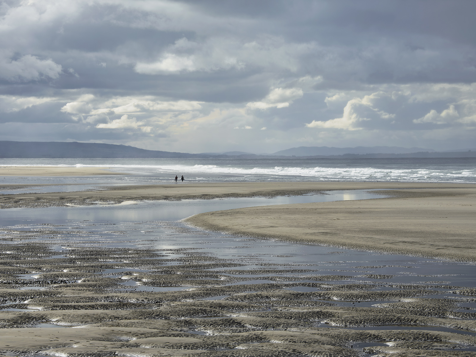 Pillows of wet sand and a tidal pool meandering its way to the sea with a distant couple walking across an empty beach all of...