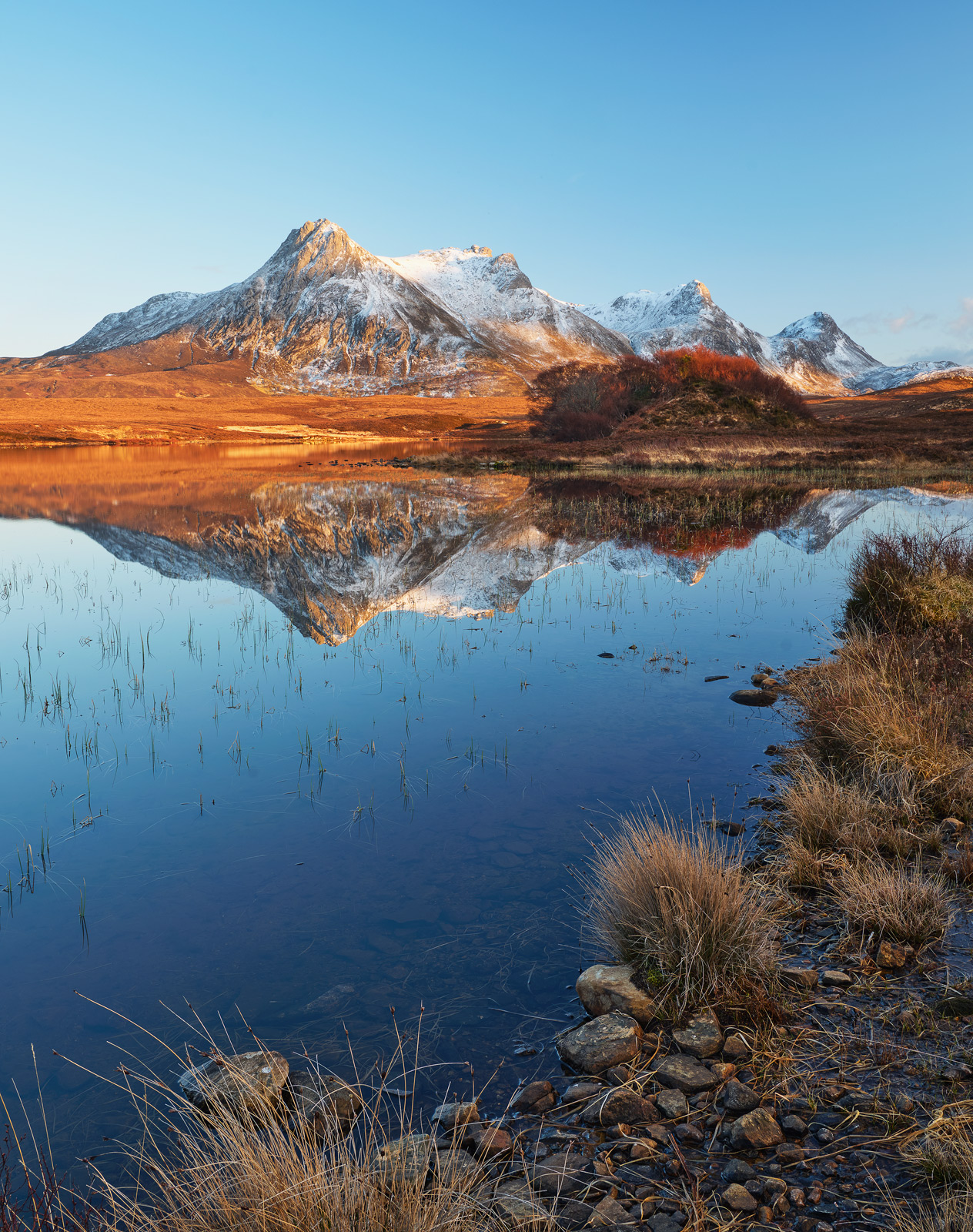 Snow dusted and lit by the fading golden light of sunset Ben Loyal and its reflection in Loch Hakel has rarely looked finer.