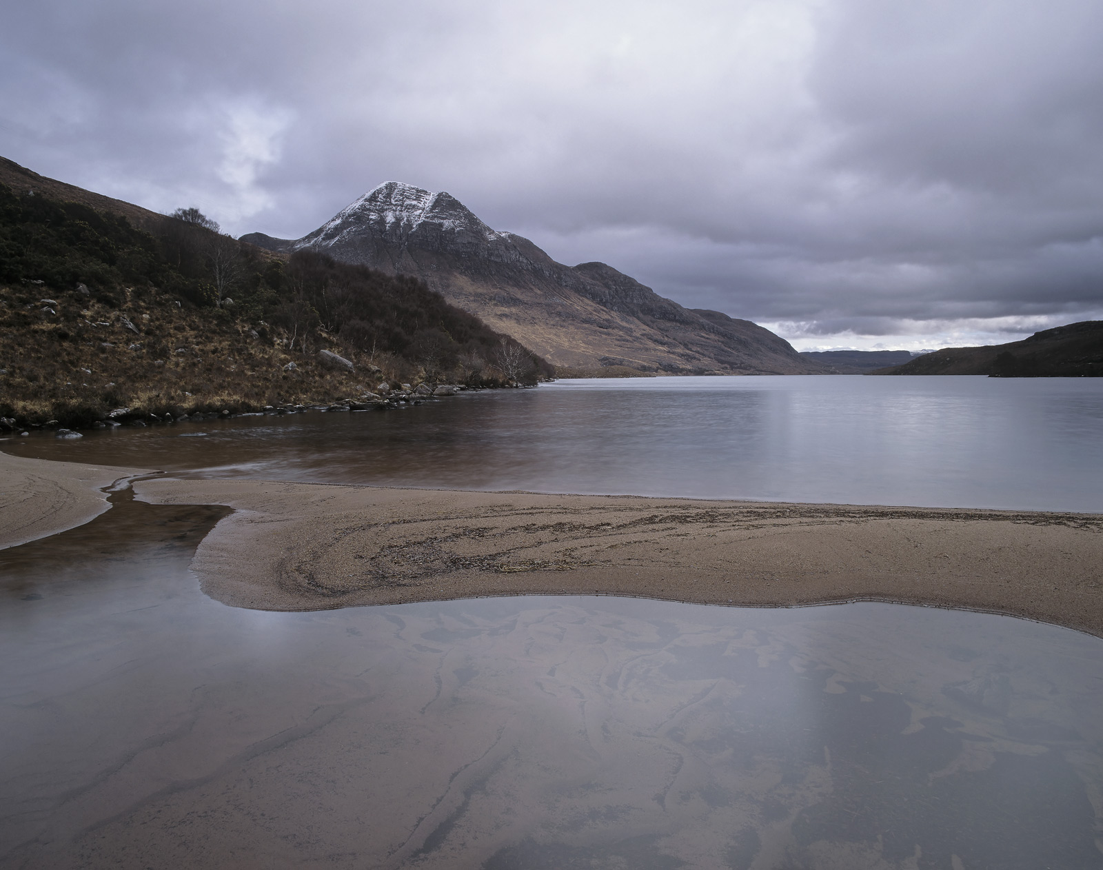 A terracotta sandbar cuts across the moody blue and steely grey reflected sky of a winter afternoon at Loch Lurgainn right...